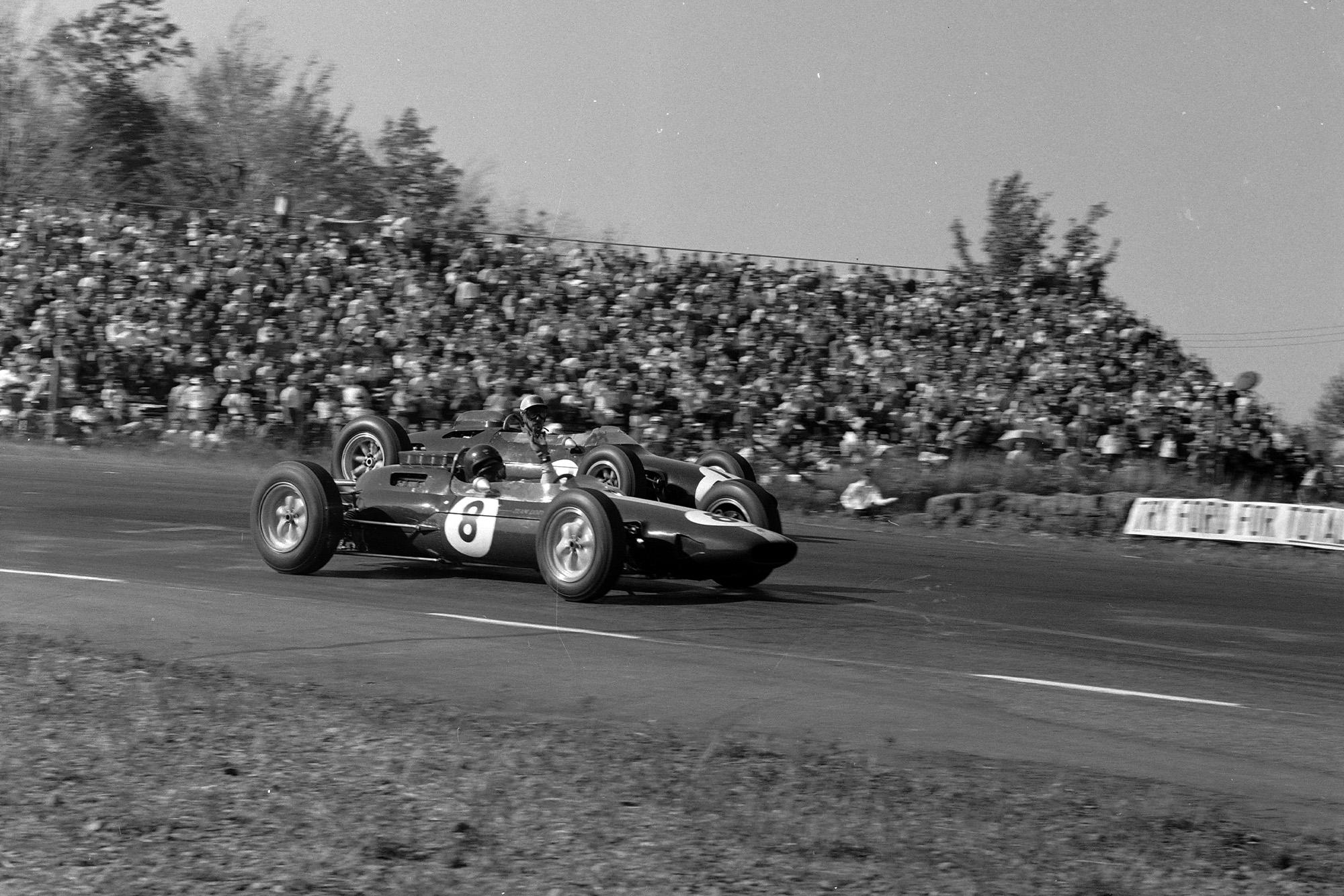 Jim Clark, Lotus 25 Climax, signals as he passes Jo Bonnier, Cooper T66 Climax.
