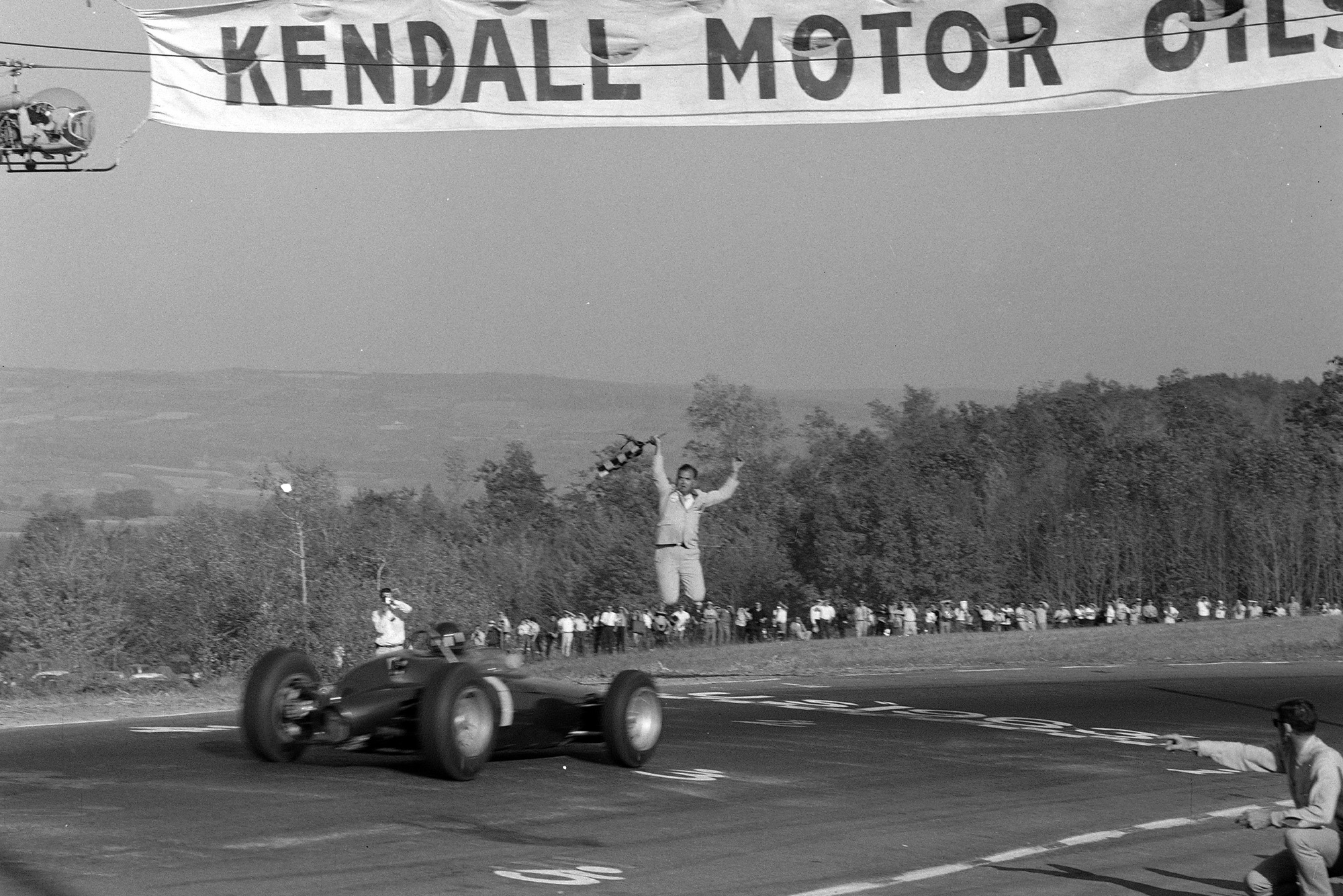 Graham Hill, BRM P57, crosses the finish line to finish 3rd.