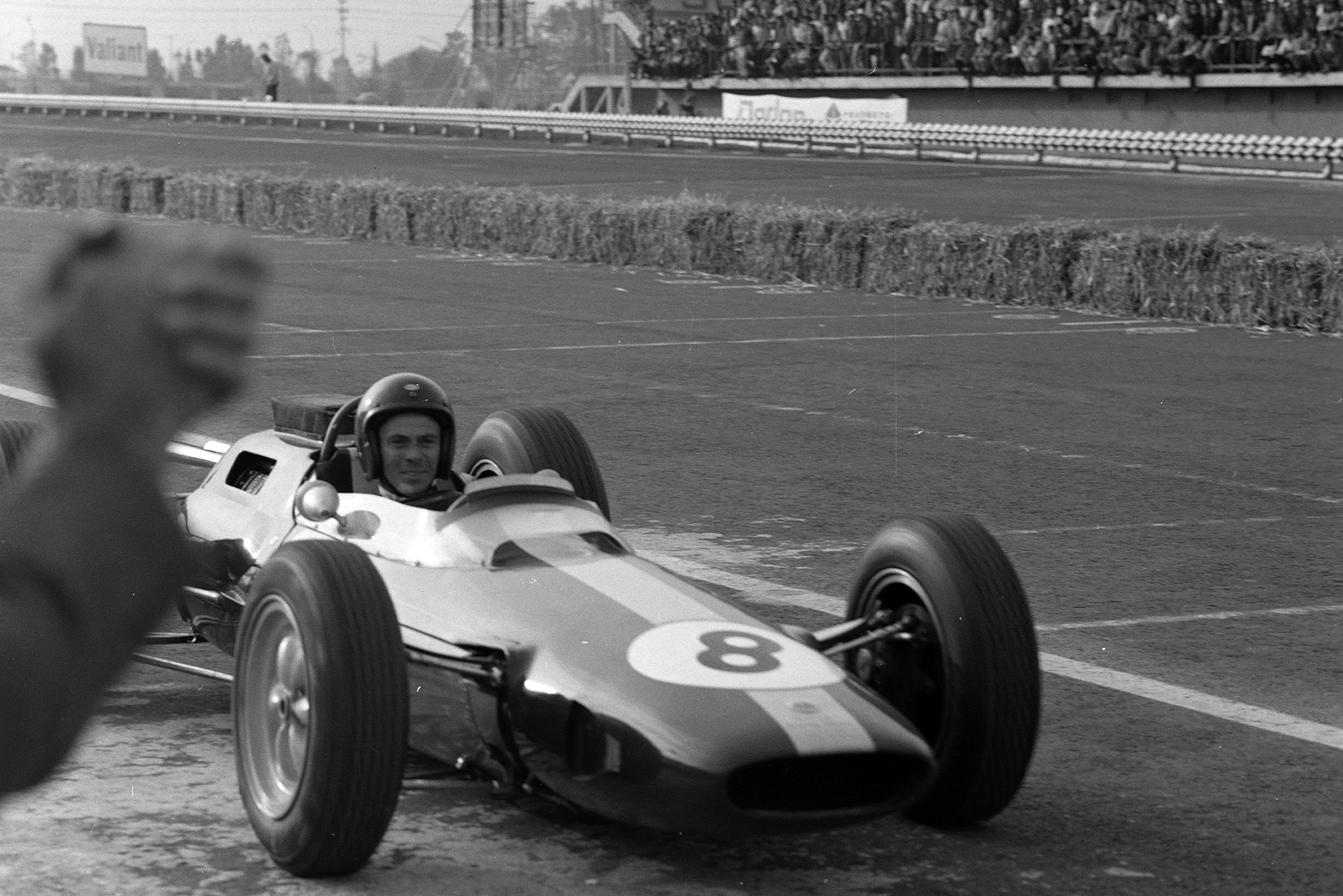 Jim Clark, Lotus 25 Climax, pulls into the pitlane after the race.