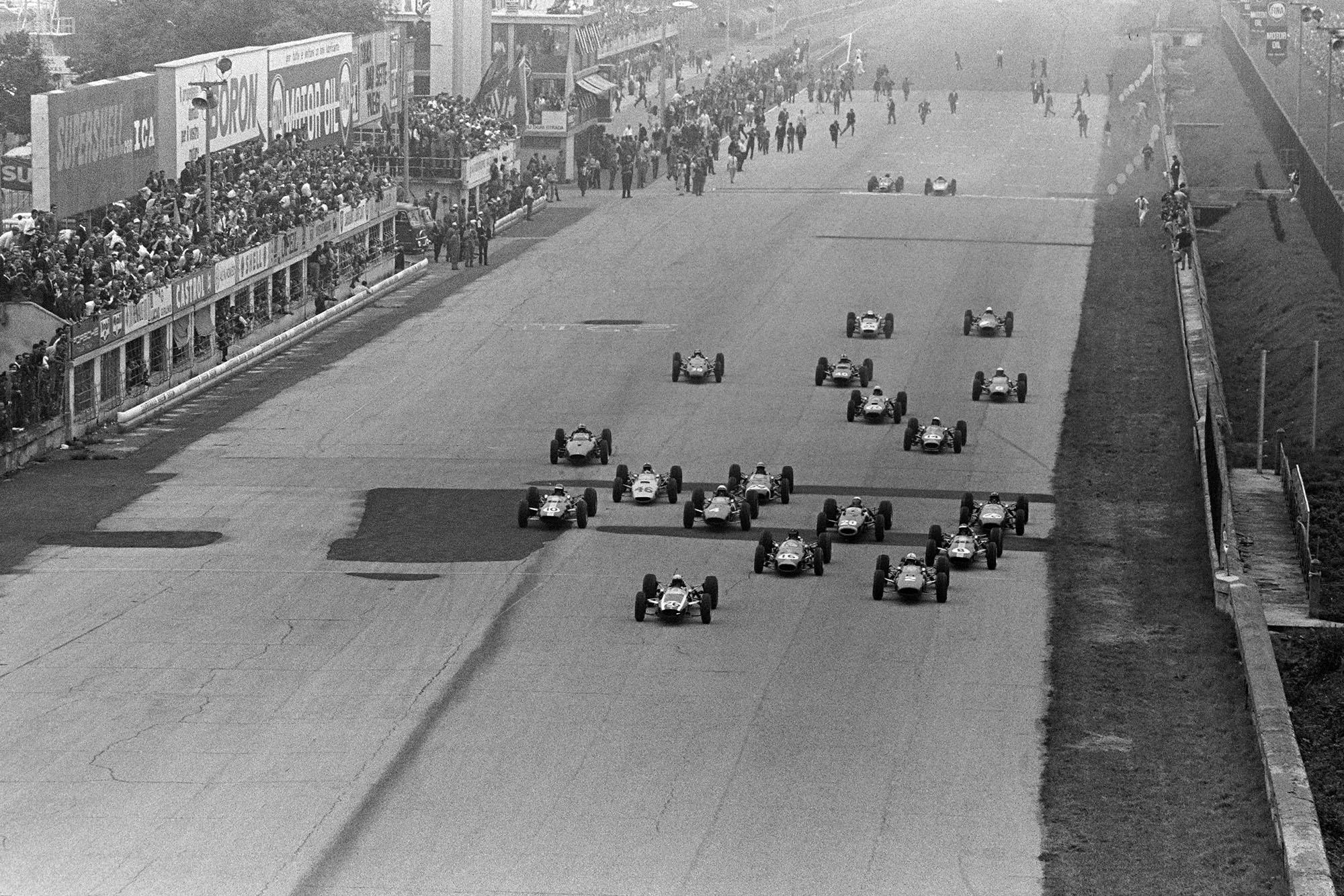 The start of the race. Bruce McLaren, Cooper T73 Climax, John Surtees, Ferrari 158, and Dan Gurney, Brabham BT7 Climax, do battle at the front.