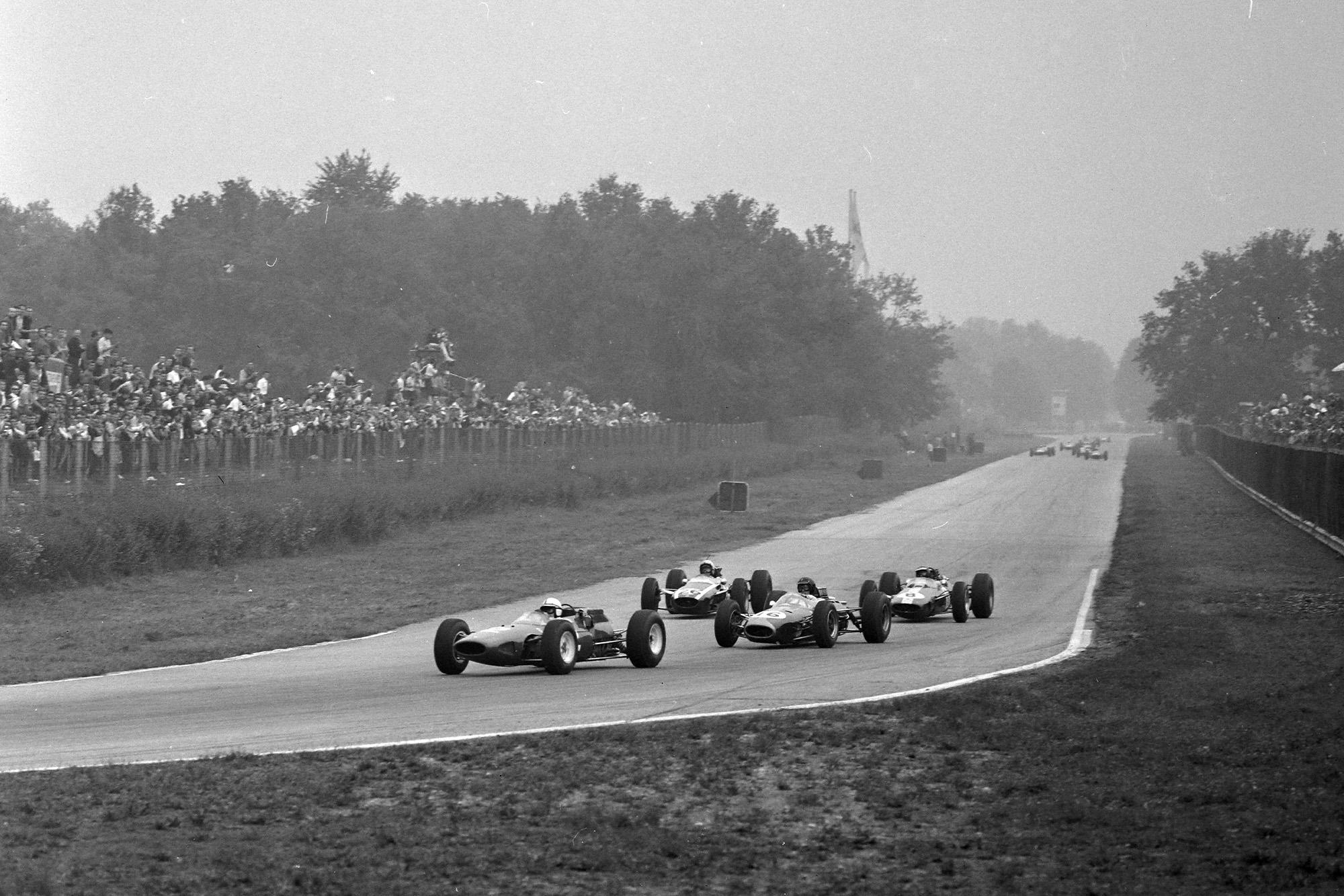 John Surtees, Ferrari 158, leads Dan Gurney, Brabham BT7 Climax, Bruce McLaren, Cooper T73 Climax, and Jim Clark, Lotus 33-Climax