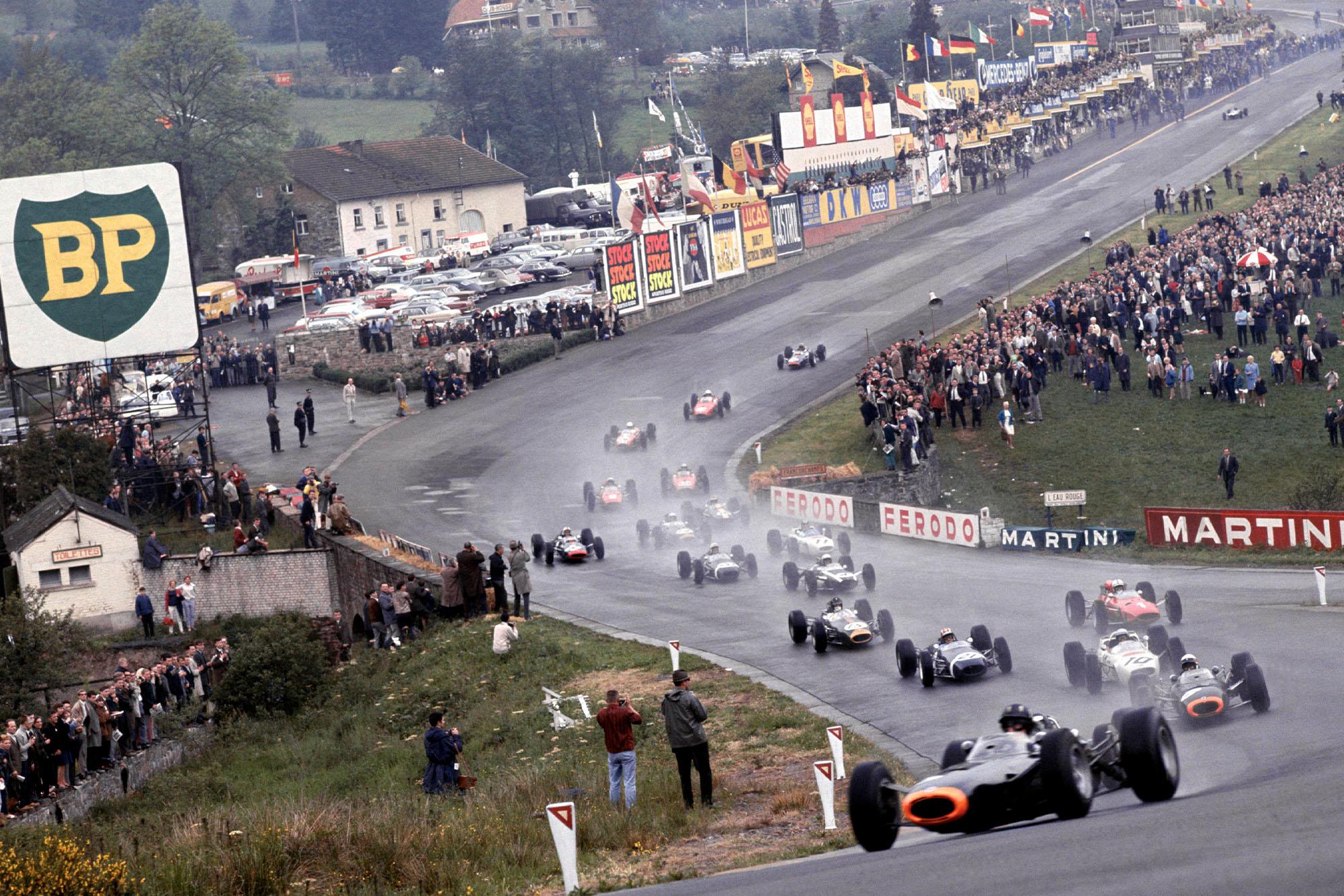 Graham Hill leads Jackie Stewart (Both BRM P261's), Richie Ginther (Honda RA272), Jo Siffert (Brabham BT11 BRM), John Surtees (Ferrari 158), Dan Gurney (Brabham BT11 Climax) and the rest of the field through Eau Rouge at the start.