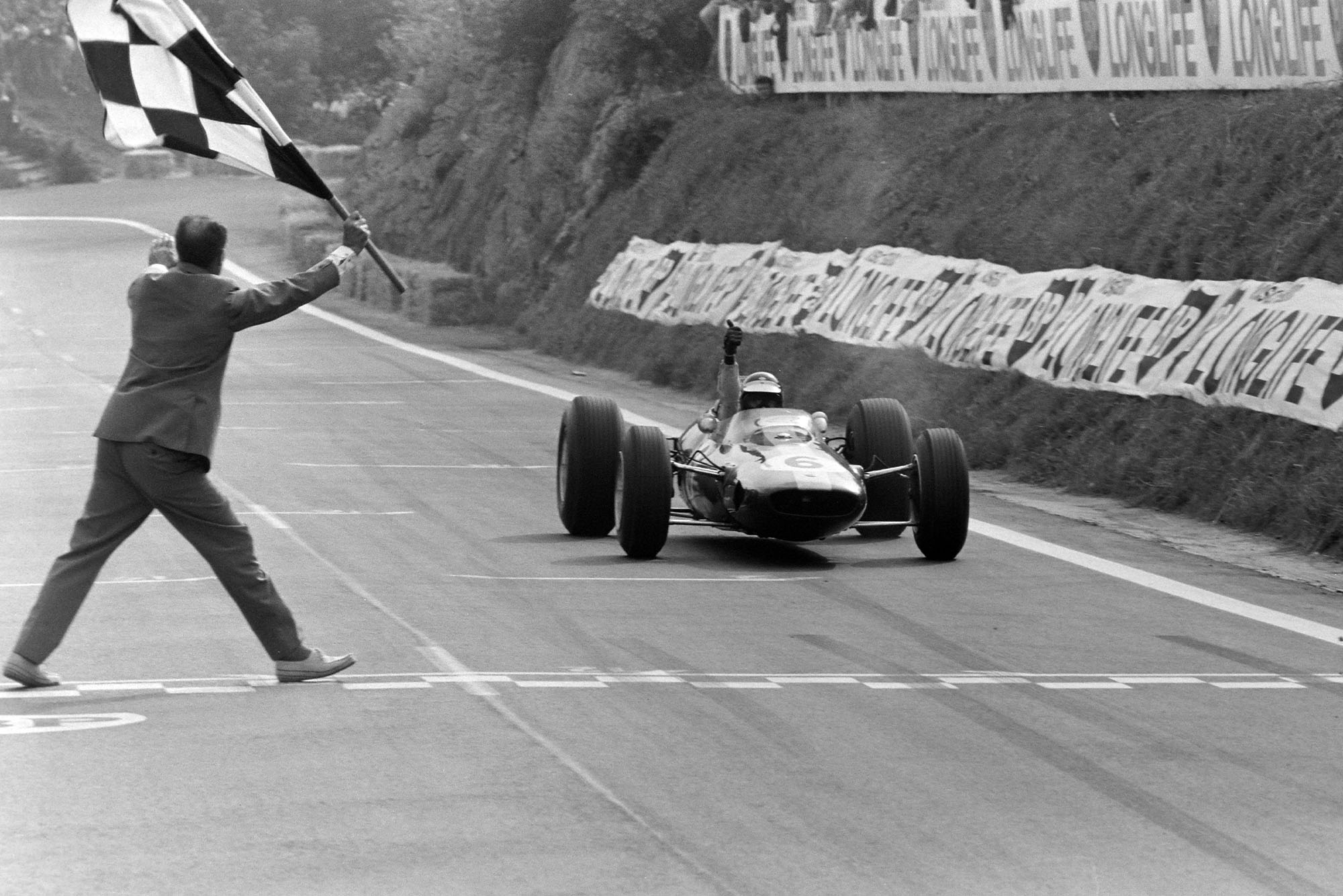 Jim Clark, Lotus 25 Climax, gives a thumbs up as he takes the chequered flag.