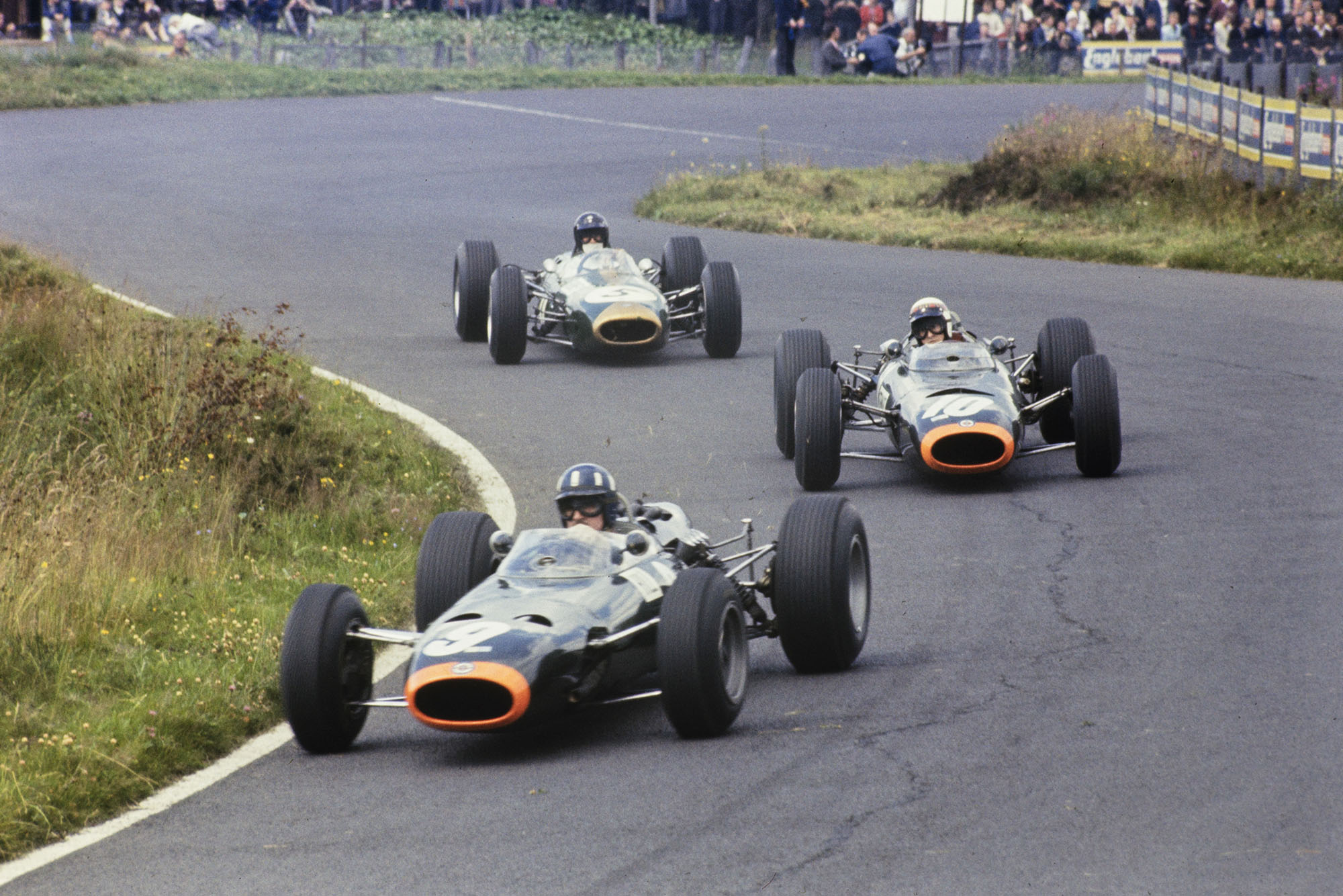 Graham Hill, BRM P261, leads Jackie Stewart, BRM P261, and Dan Gurney, Brabham BT11 Climax.