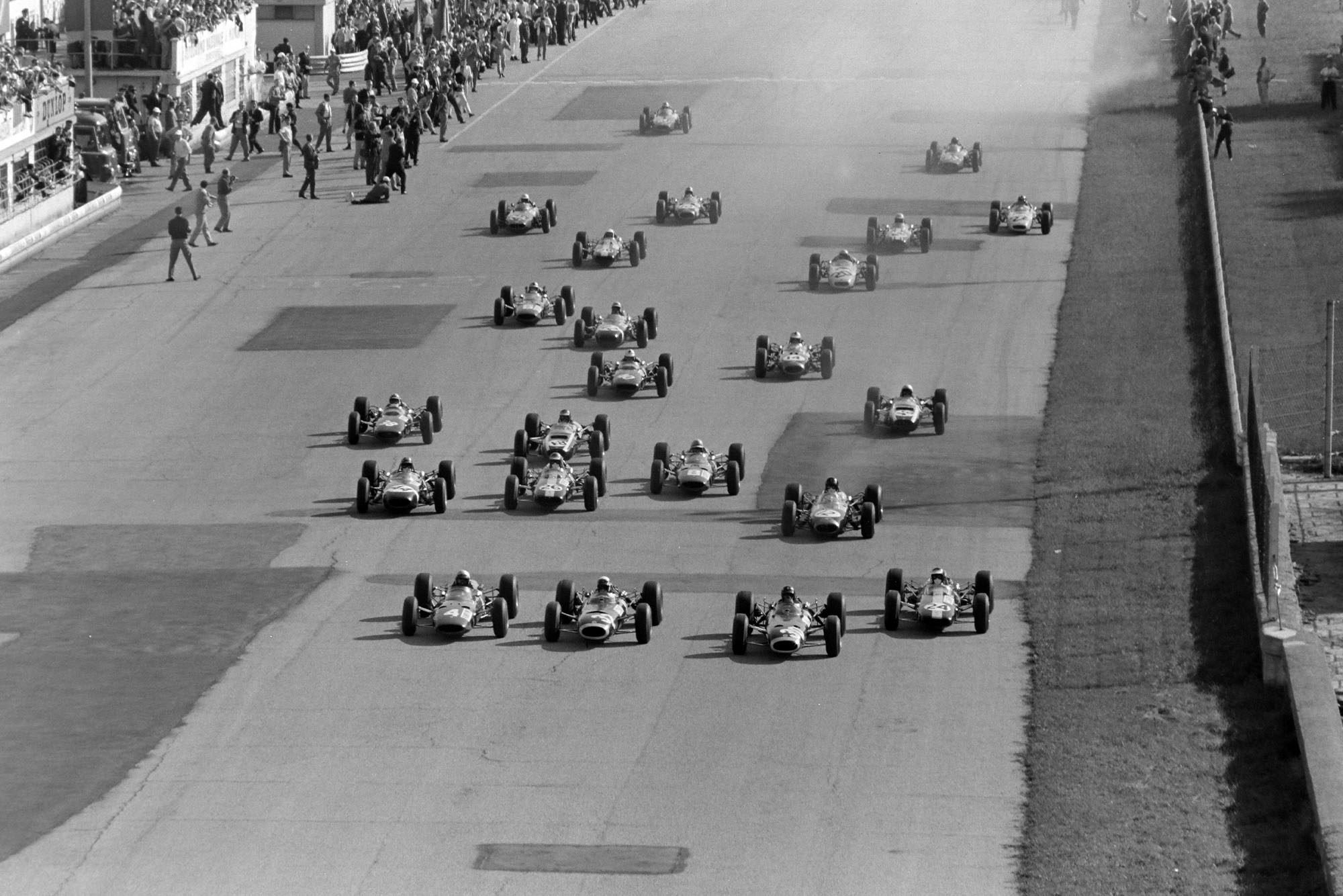 The start of the race. Lorenzo Bandini, Ferrari 1512, battles with Jackie Stewart, BRM P261, Graham Hill, BRM P261, and Jim Clark, Lotus 33 Climax, heading towards the first turn.