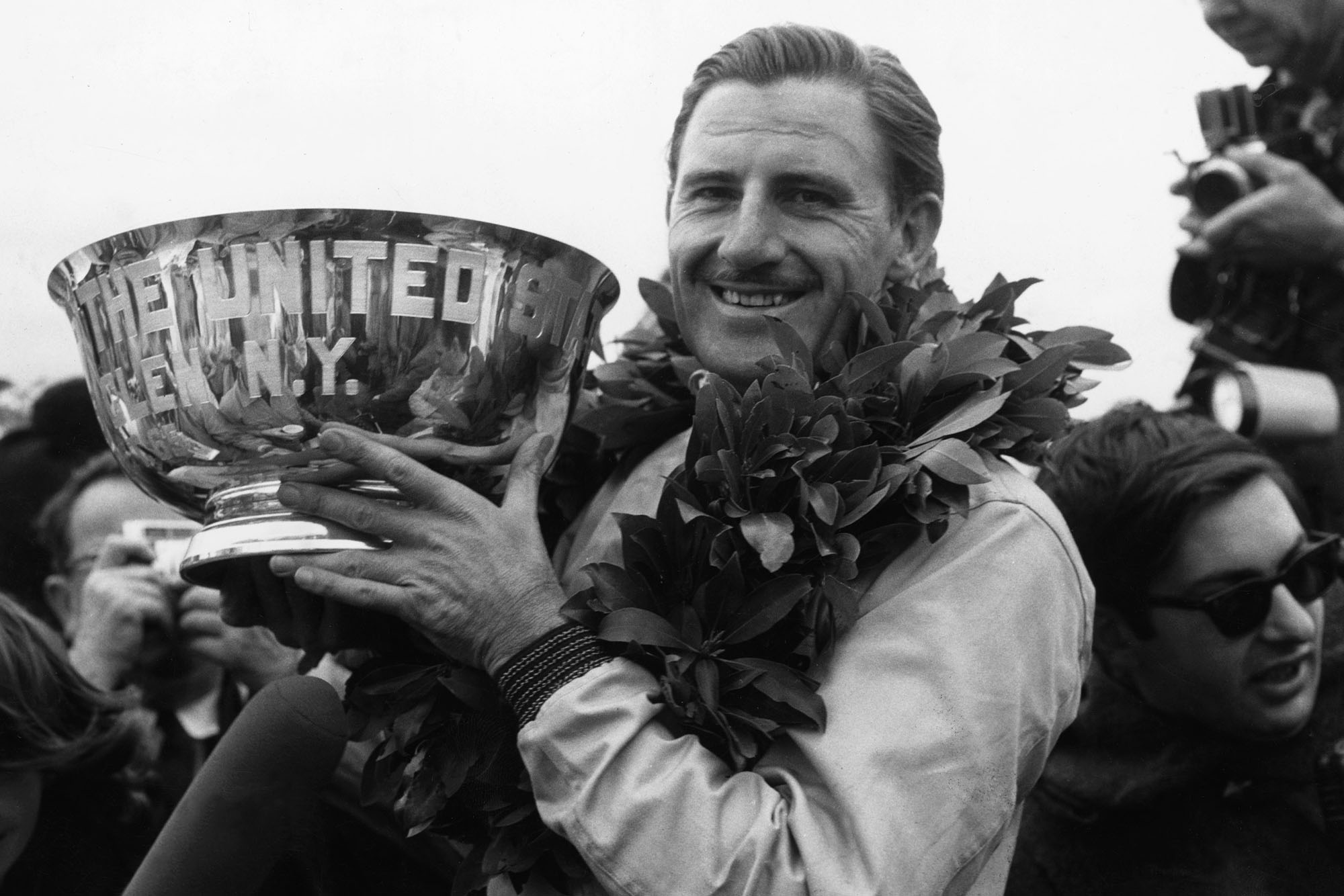 Graham Hill, BRM P261, holds his winner's trophy aloft.