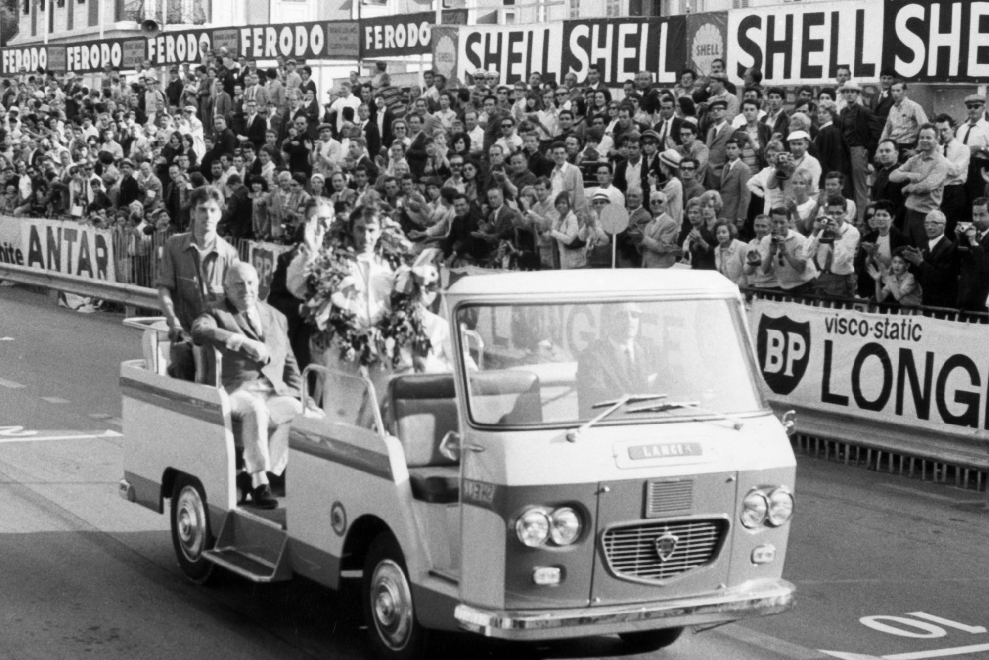 Jackie Stewart, BRM P261, 1st position, waves to the crowd on his victory parade.