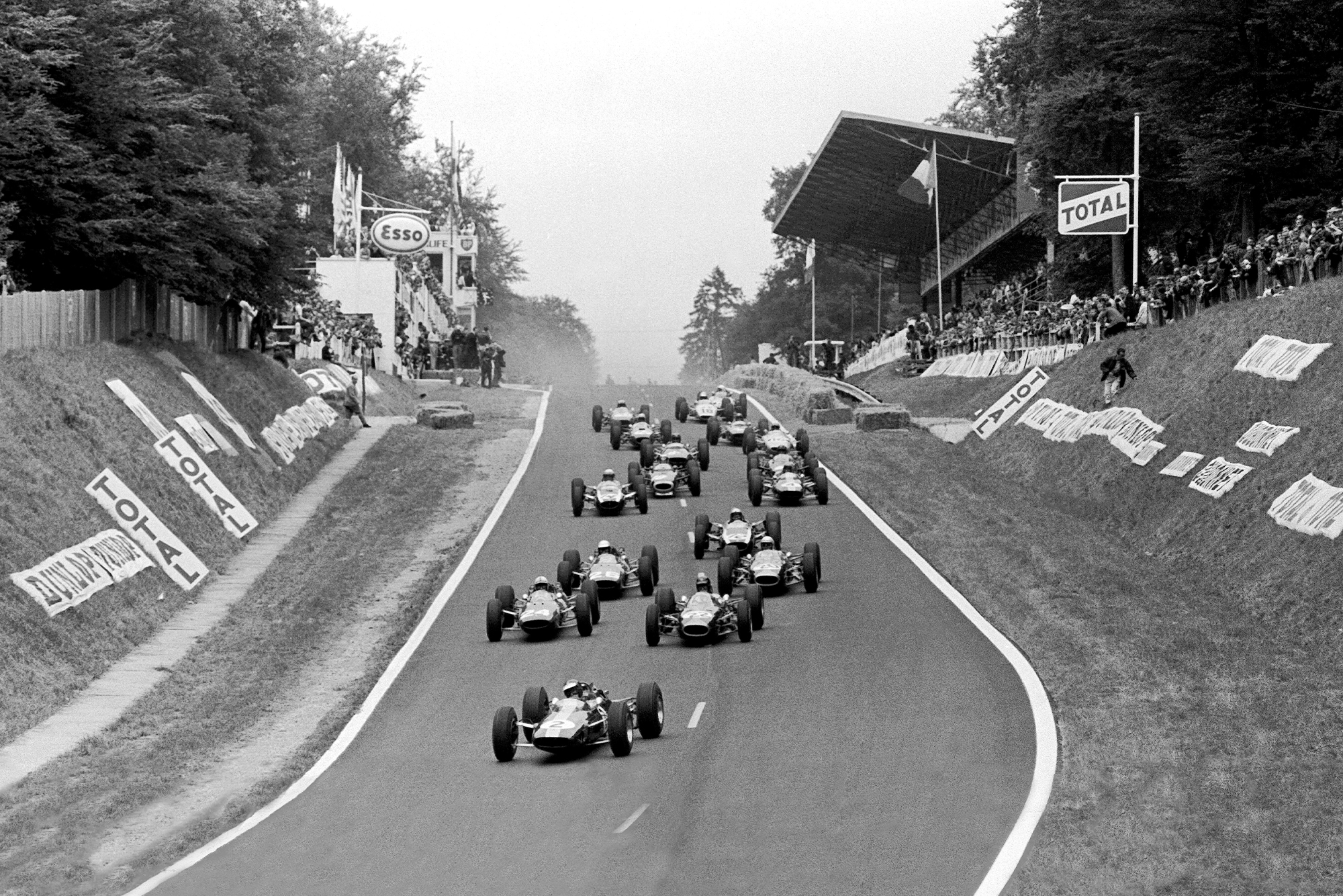 Jim Clark, Lotus 25 Climax, leads Dan Gurney, Brabham BT7 Climax, and John Surtees, Ferrari 158, as the field follow behind.