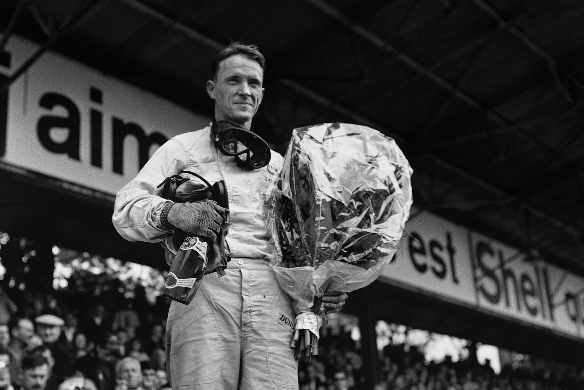 Brabham's Dan Gurney stands on the podium, champagne and bouquet in hand.