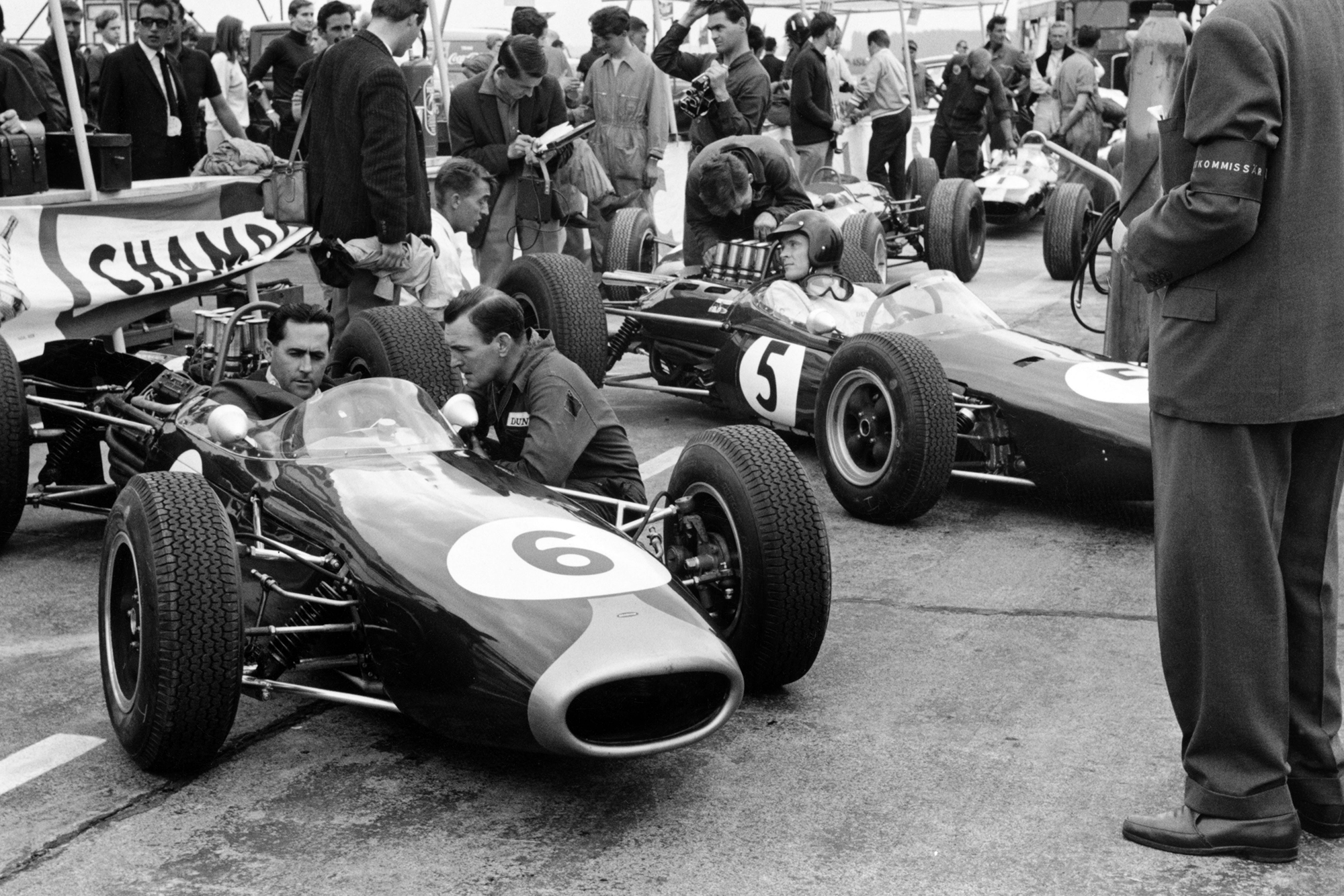 Jack Brabham (Brabham BT11 Climax) and Dan Gurney (Brabham BT7 Climax) wait in the pits