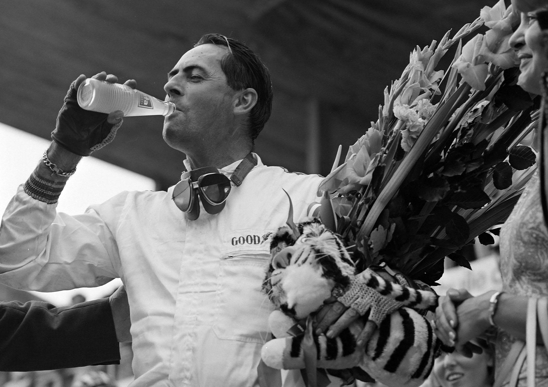 Race winner Jack Brabham celebrates with a drink on the podium.