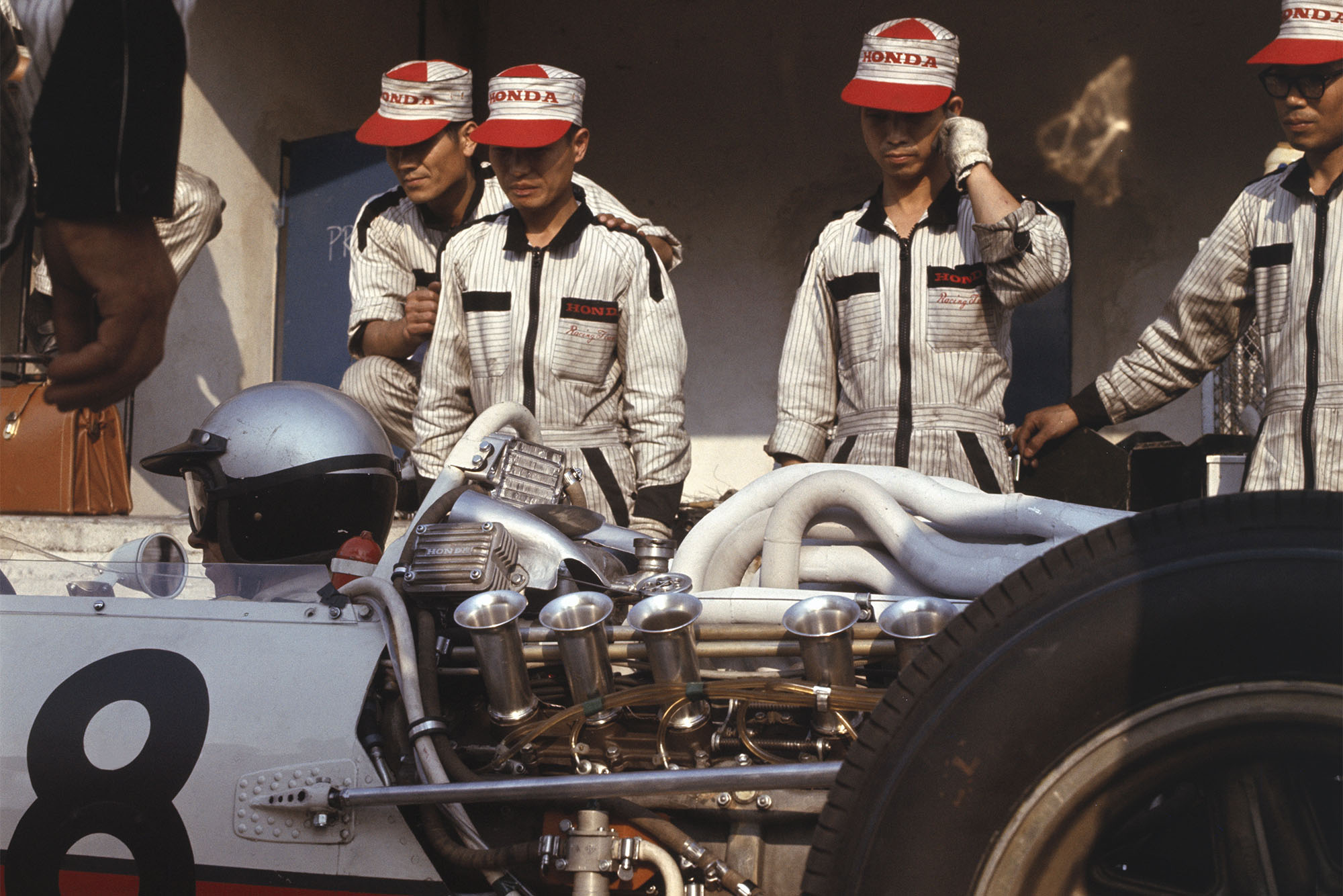 Richie Ginther (Honda RA273) is discussed by the mechanics.