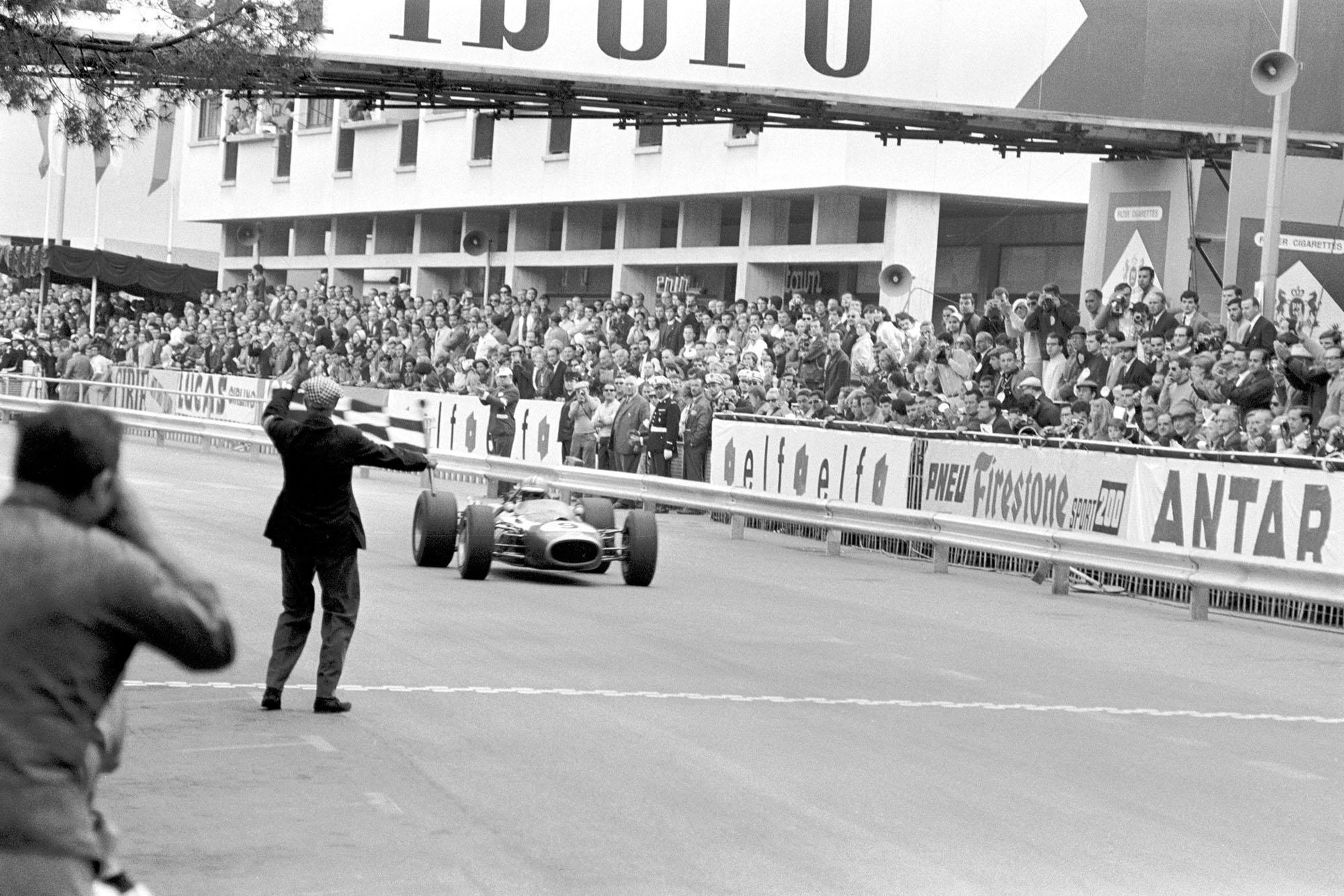 Denny Hulme (NZL) Brabham BT20 takes the chequered flag to win the Monaco Grand Prix.