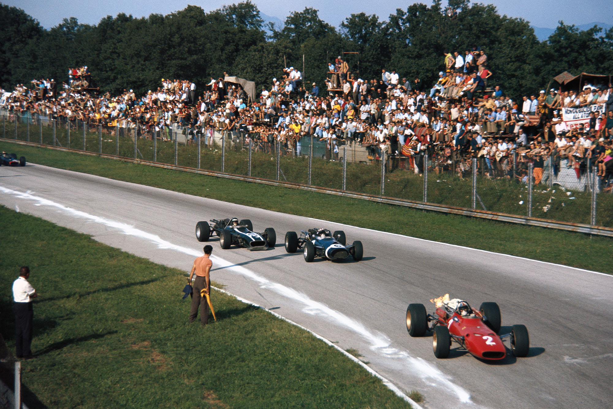 Chris Amon, Ferrari 312, leads Jo Siffert, Cooper T81 Maserati, and Jochen Rindt, Cooper T86 Maserati, into Parabolica.