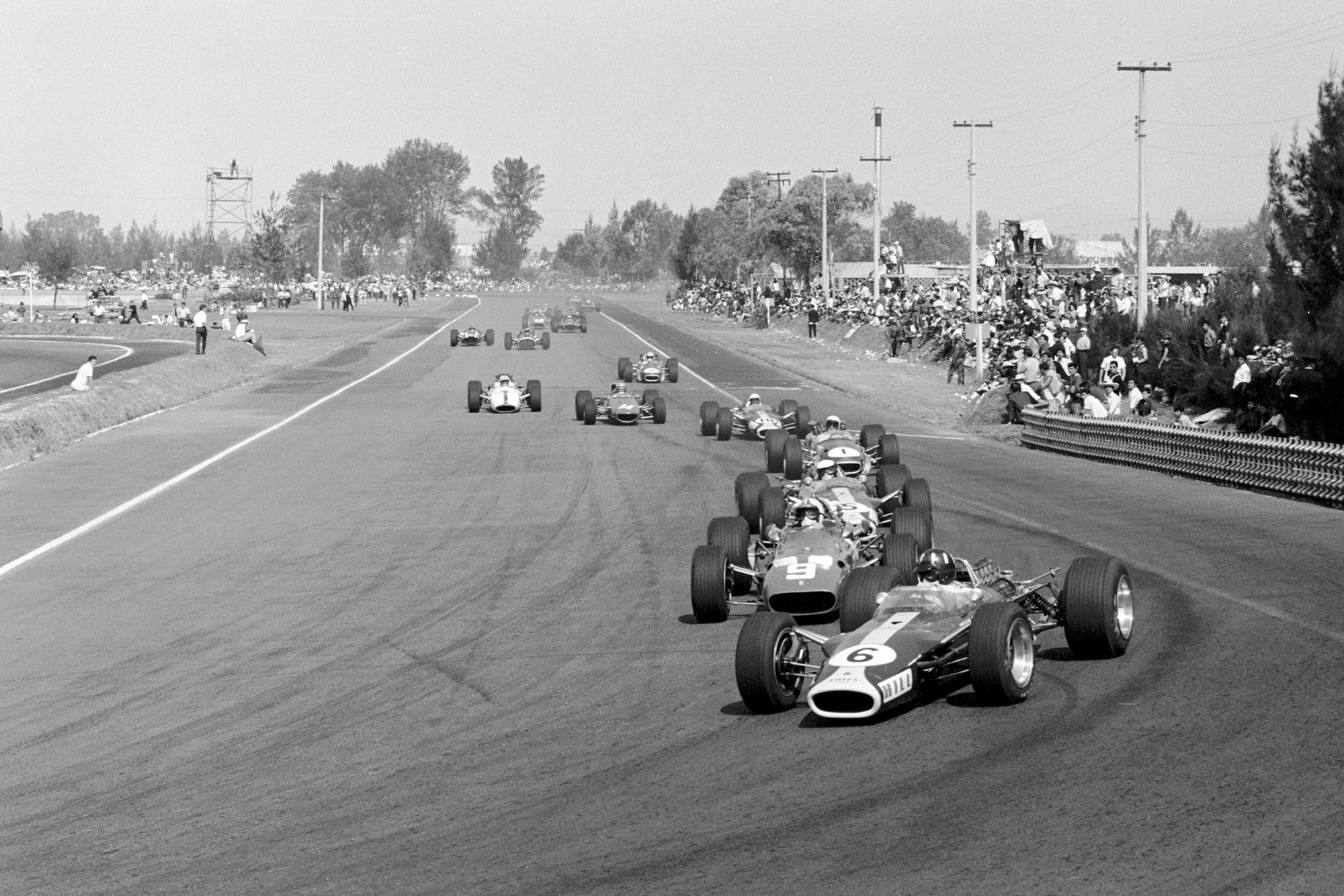 In the opening lap of the race, Graham Hill (GBR) Lotus 49 leads Chris Amon (NZL) Ferrari 312 with race winner Jim Clark (GBR) Lotus 49 in third place. Mexican Grand Prix, Mexico City, 22 October 1967.
