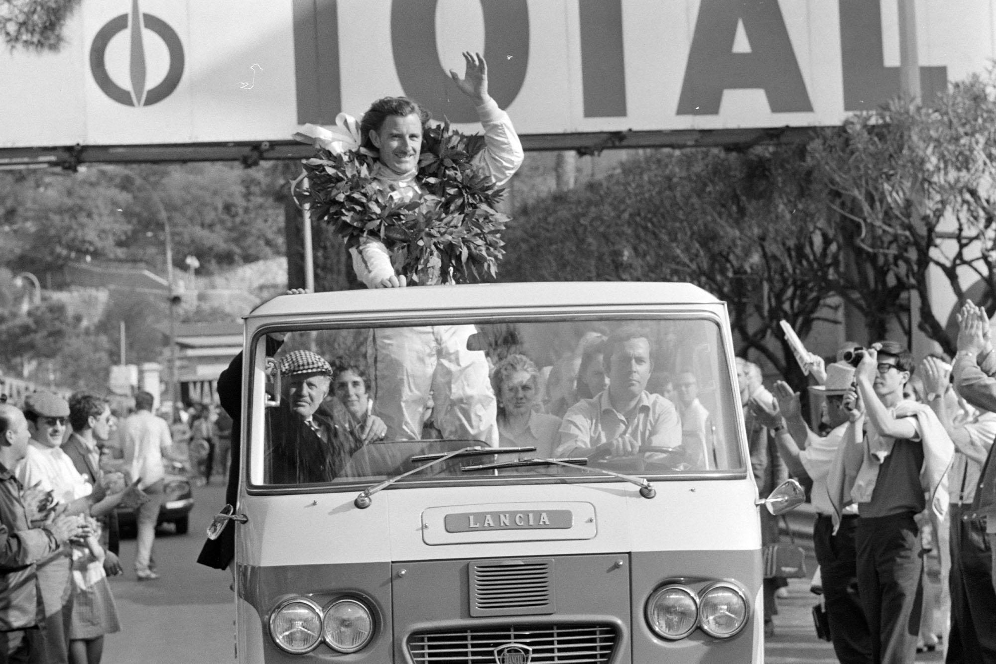 Graham Hill celebrates victory on the parade lap.
