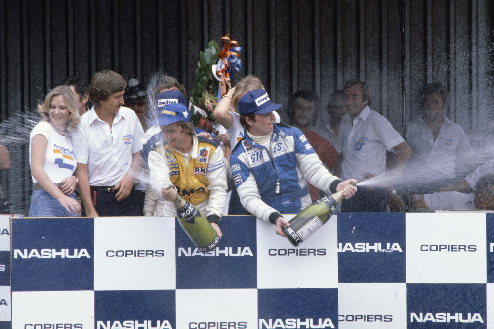Rene Arnoux (Equipe Renault) celebrates his 1st position on the podium with Patrick Depailler (Ligier Ford) 3rd position.