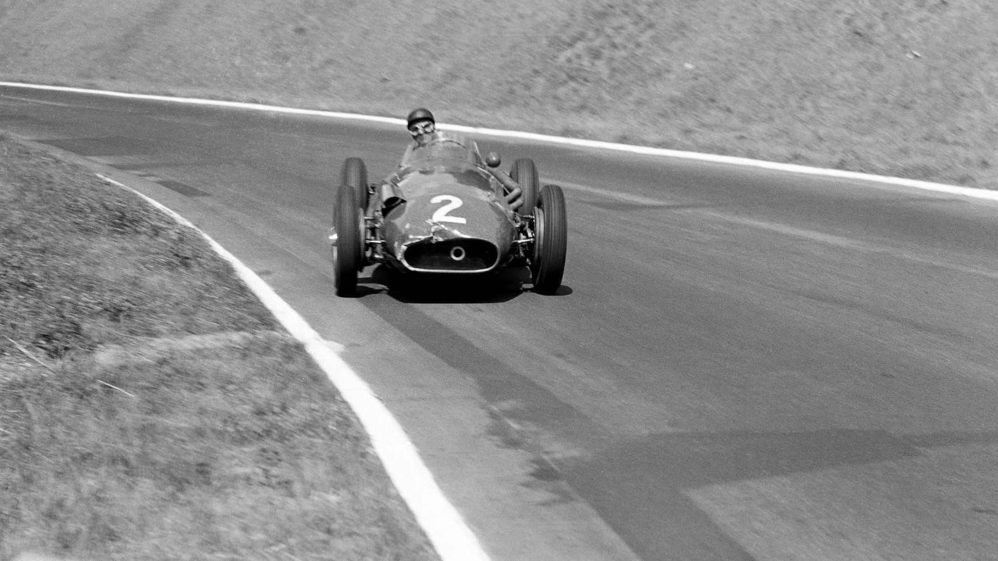Juan Manuel Fangio sliding down the hill at Rouen les Essarts in 1957