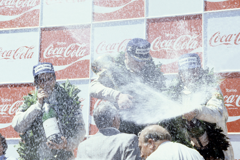 Alan Jones (Williams FW07-Ford Cosworth), 1st position and Nelson Piquet (Brabham BT49-Ford Cosworth), 2nd position, and Keke Rosberg (Fittipaldi F7-Ford Cosworth), 3rd position on the podium.