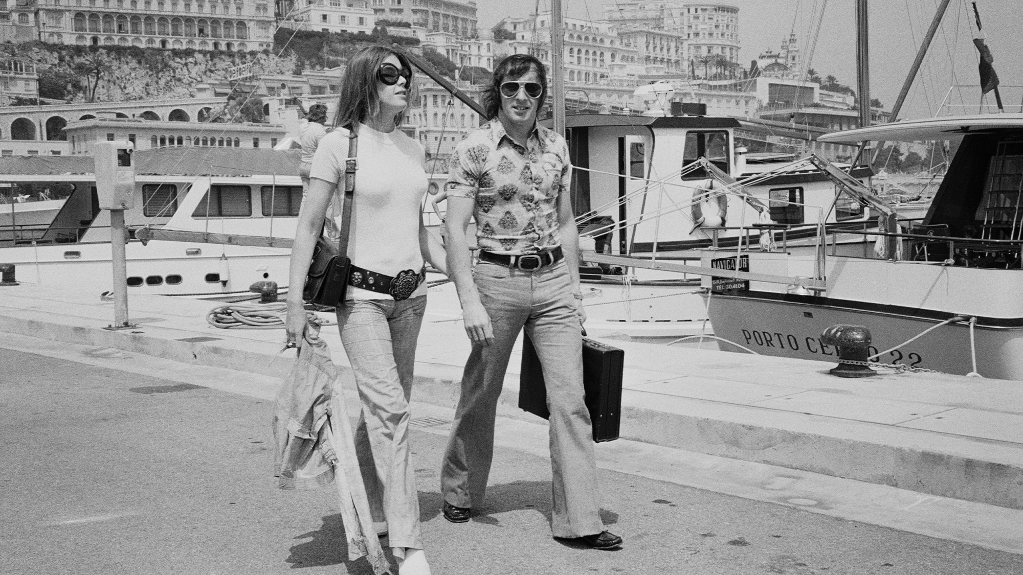 Jackie and Helen Stewart walk alongside Monaco harbour in 1971