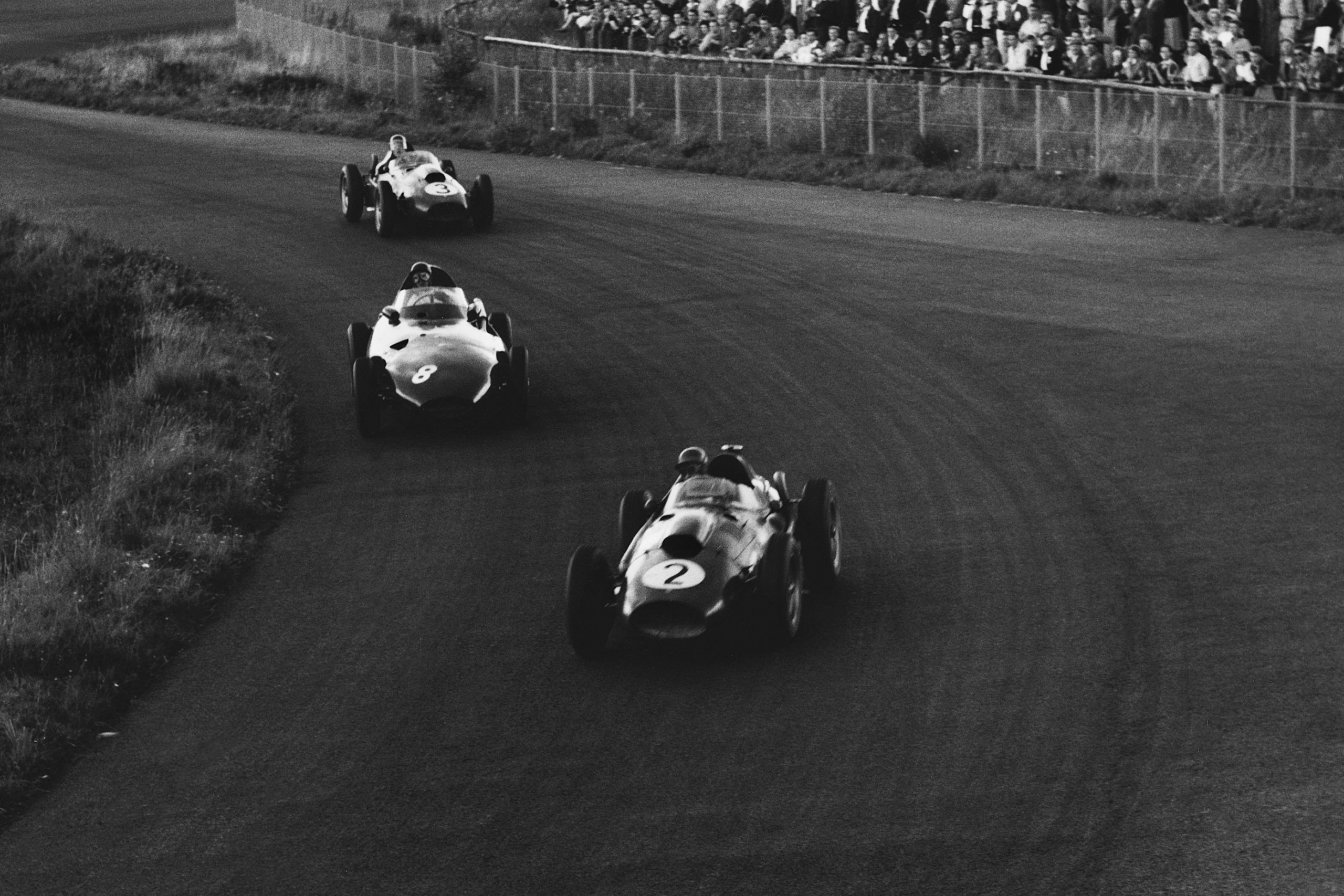 Peter Collins in his Ferarri Dino 246leads Tony Brooks in a Vanwall and Mike Hawthorn in his Ferrari Dino 246.