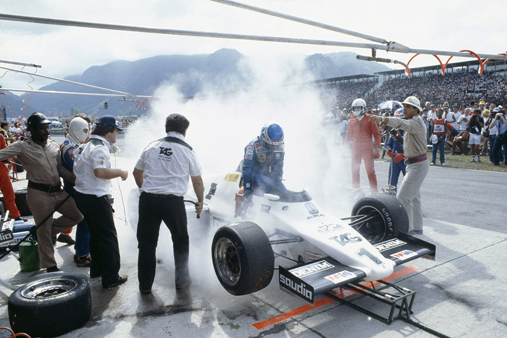 Keke Rosberg (Williams FW08C Ford) during a disastrous pitstop, where a small amount of spilt fuel caused a flash-fire which was promptly extinguished by marshals. He returned to his cockpit to finish 2nd but was disqualified for a push start after this stop.