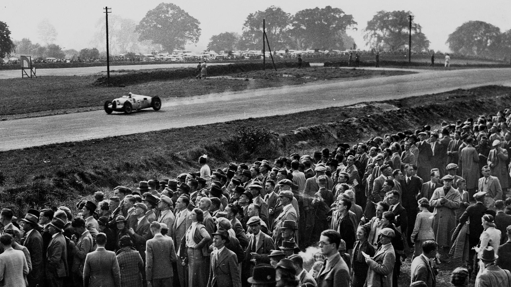 Bernd Rosemeyer drives past crowds of fans in his Auto Union at the 1937 Donington Grand Prix