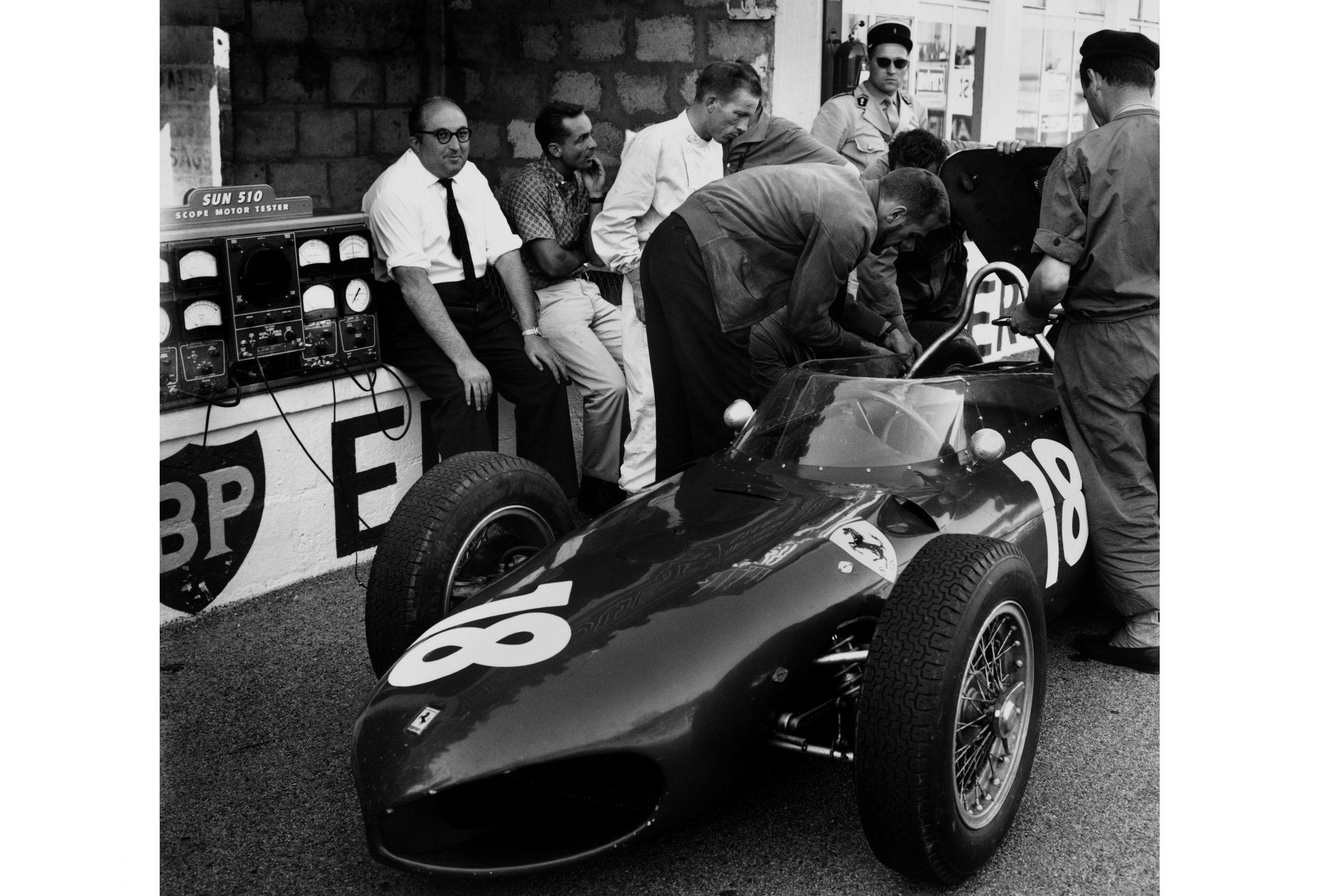 Carlo Chiti, Ferrari engine designer sitting on the pit wall with Phil Hill and Richie Ginther.
