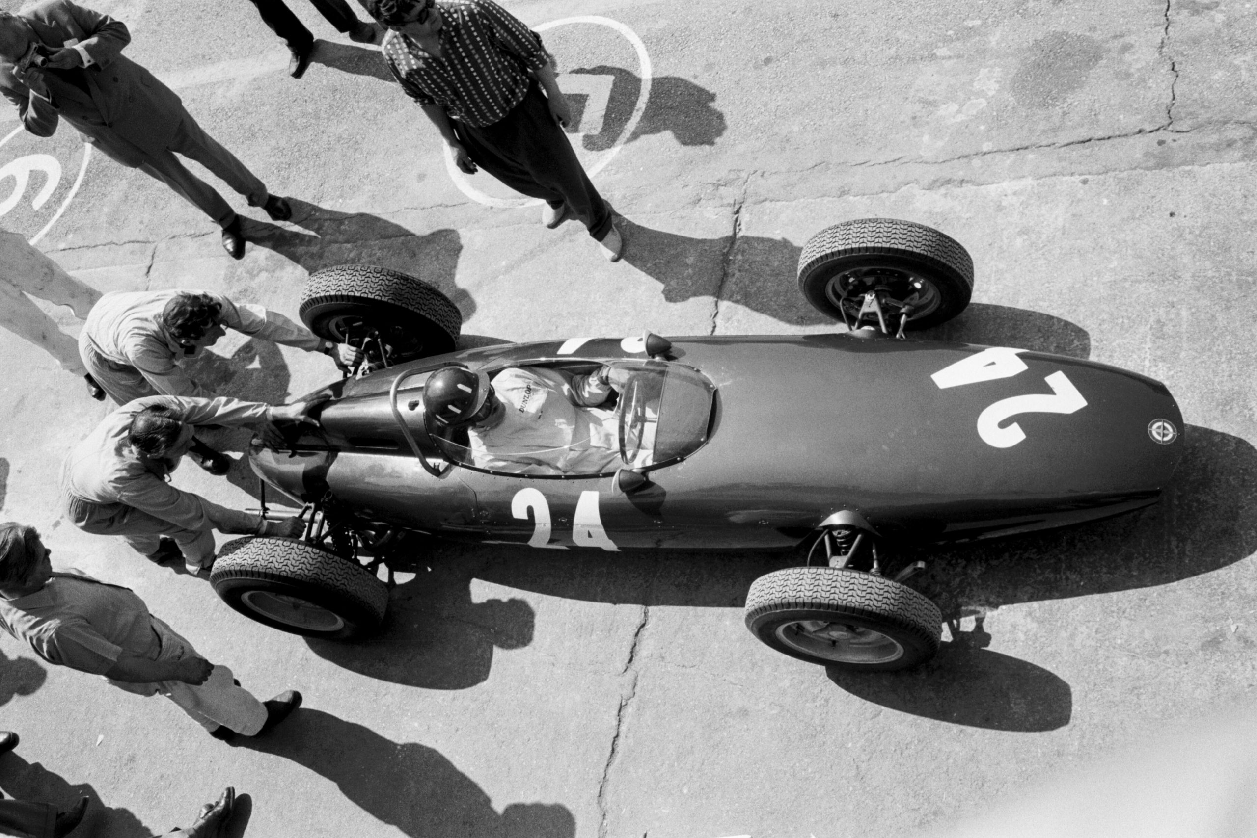 Graham Hill receives a helping hand from his mechanics in the BRM P48/57.