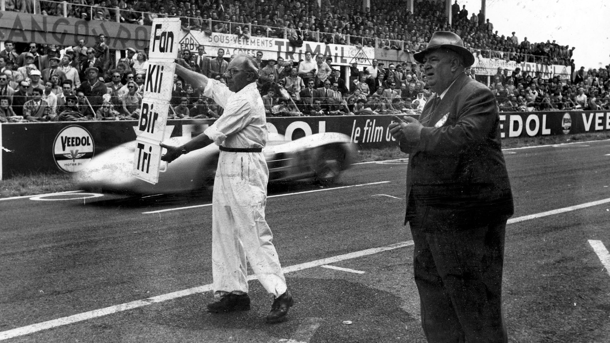 17th July 1954: Alfred Neubauer, team manager of Mercedes Benz instructs a mechanic to signal to the two Mercedes during a French Grand Prix at Reims. It was the first time German cars had competed for 15 years. Original Publication: Picture Post - 7209 - First Race Of The Mercedes - A Ruthless Triumph - pub. 1954 (Photo by Joseph McKeown/Picture Post/Hulton Archive/Getty Images)