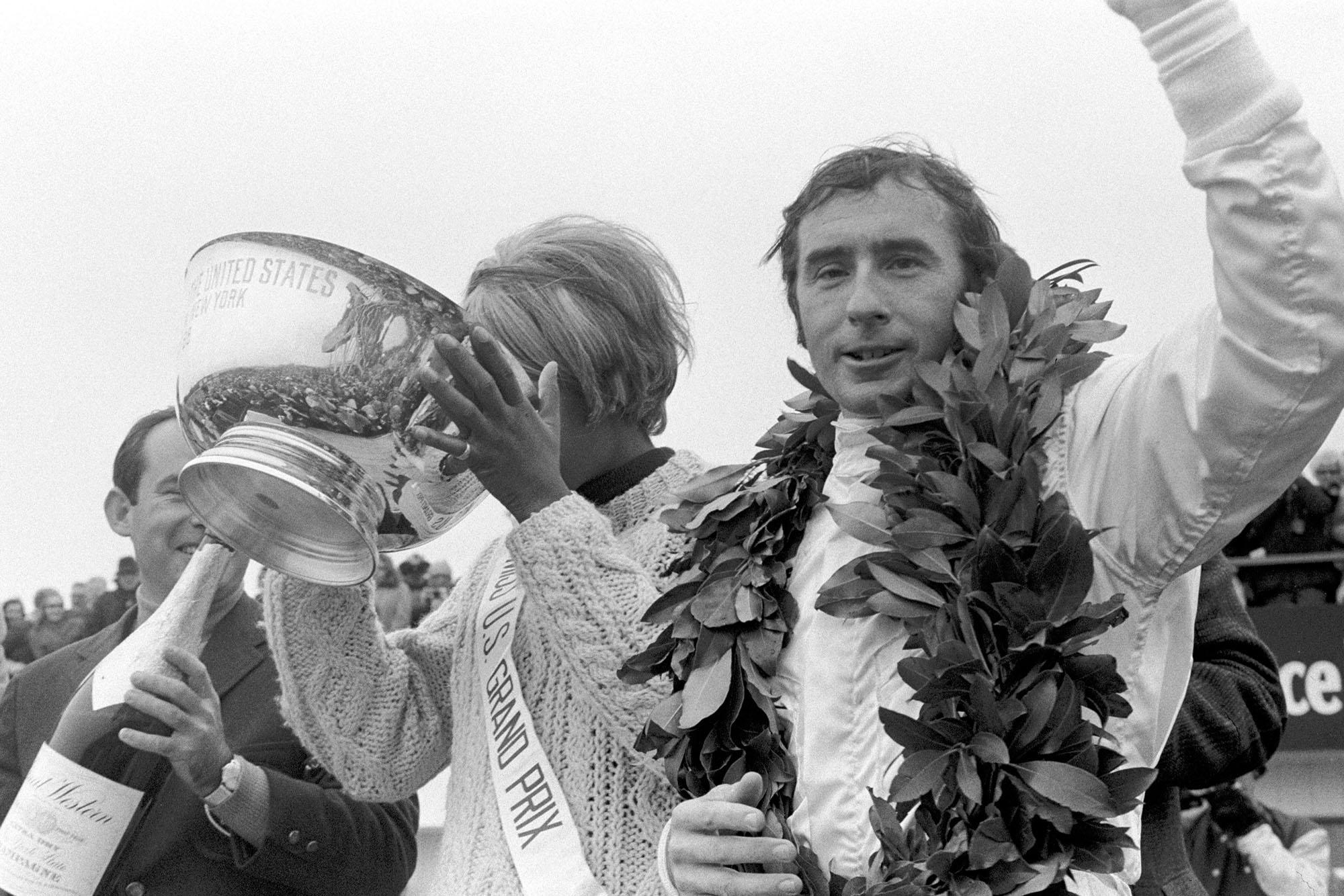 Jackie Stewart celebrates on the podium at the 1968 United States Grand Prix.