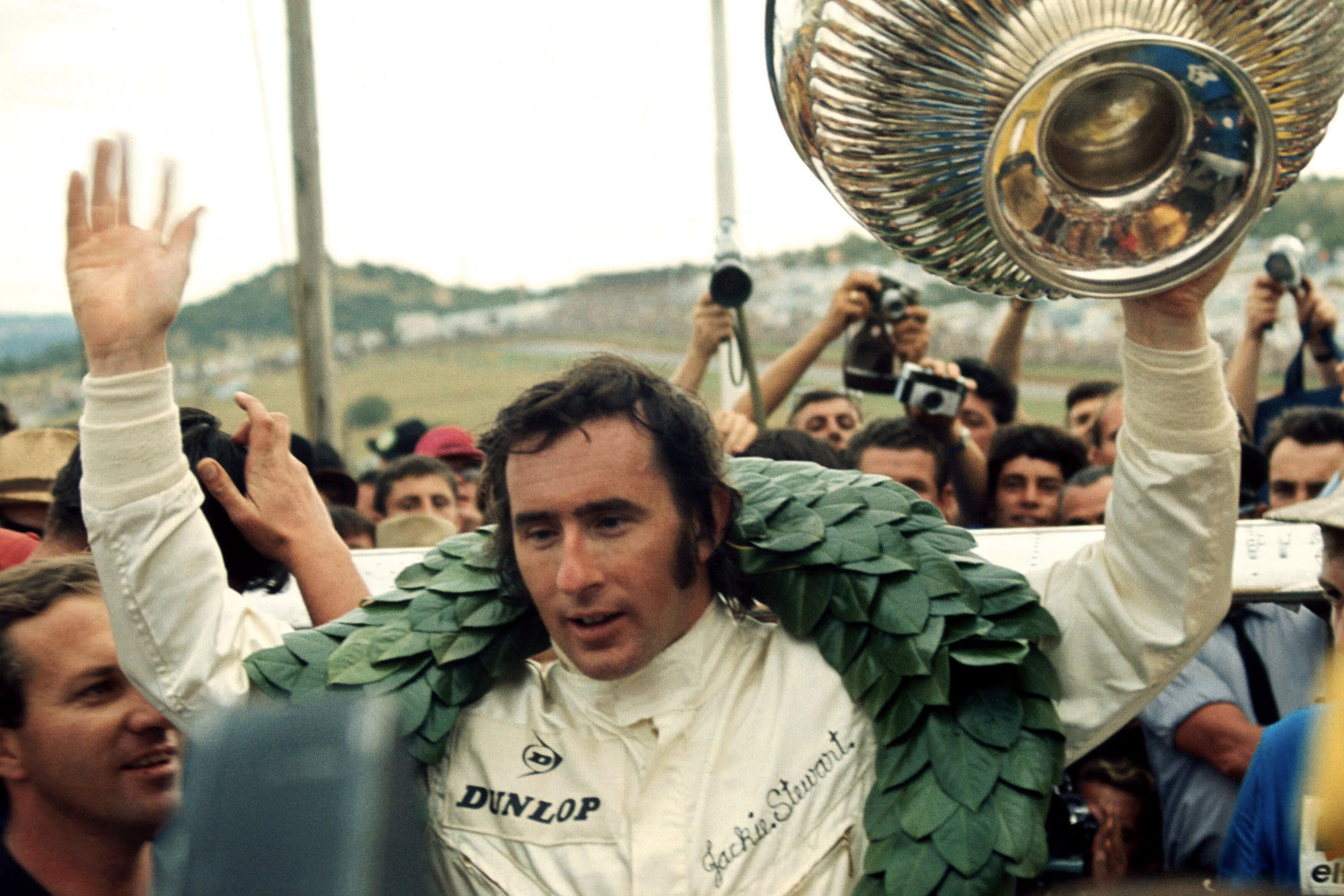 Jackie Stewart celebrates on the podium after winning the 1969 South African Grand Prix.