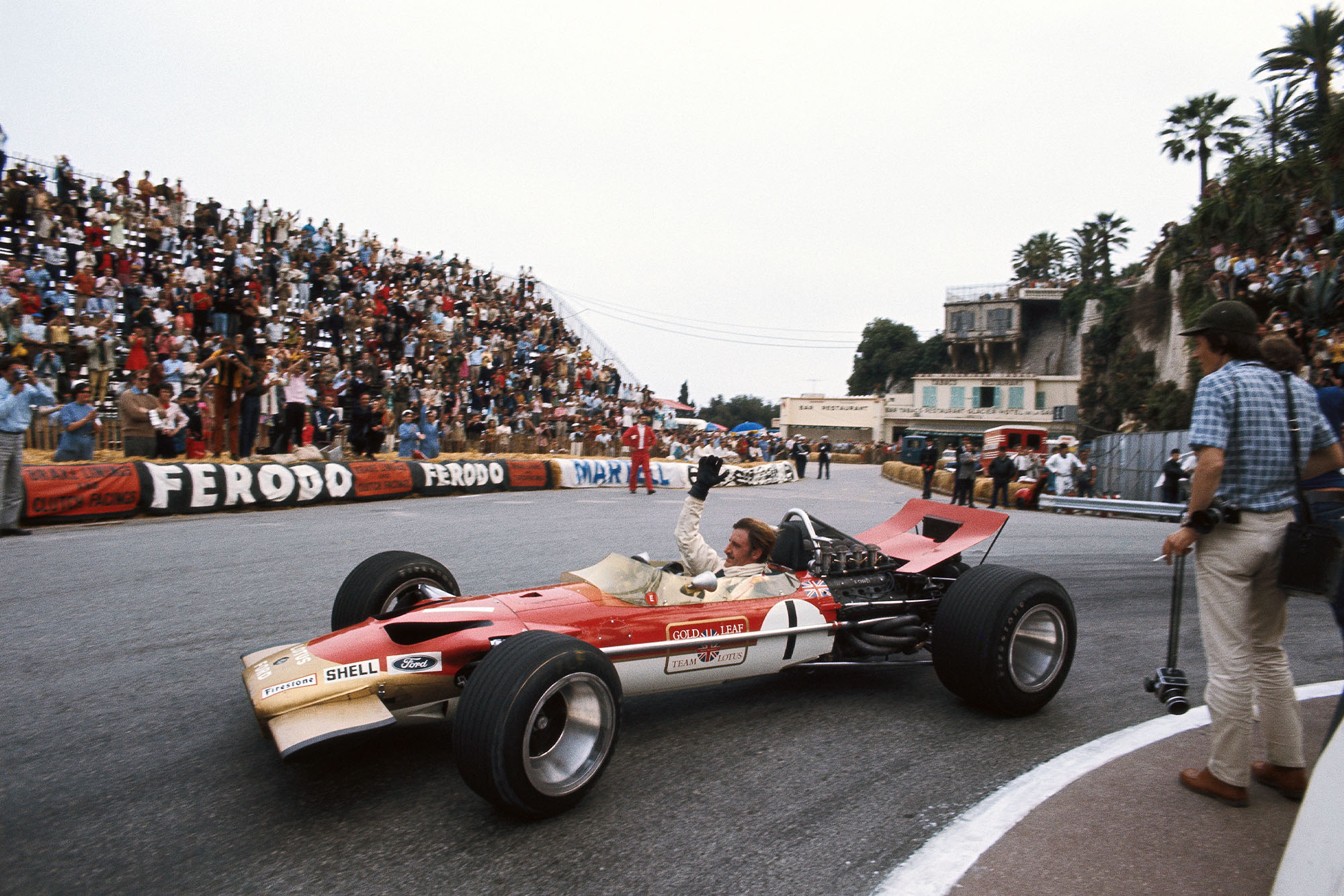 Graham Hill waves to the crowd after sealing victory