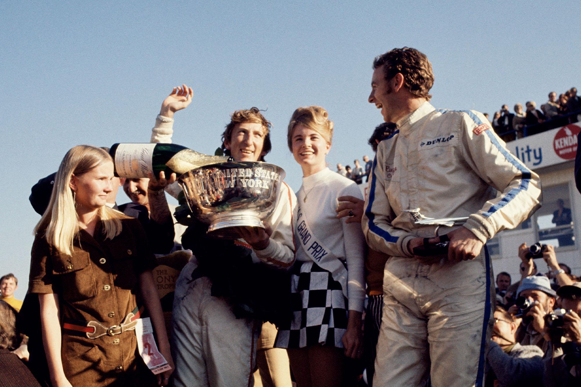 Jochen Rindt celebrates on the podium after winning the 1969 United States Grand Prix