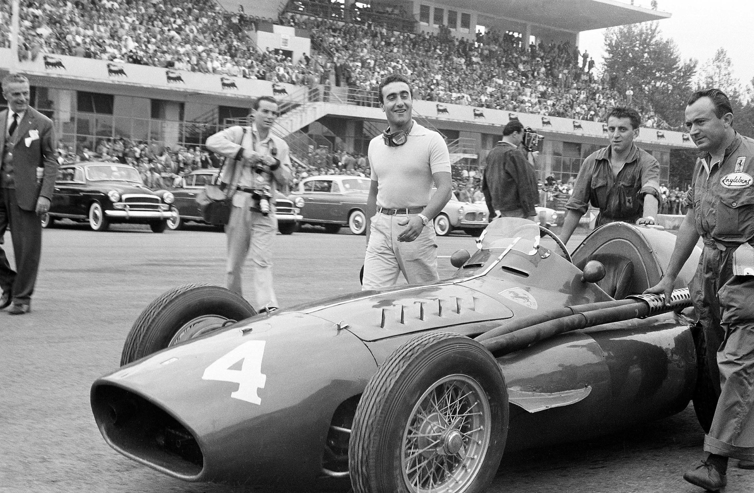 Racing driver Eugenio Castellotti with his Ferrari 'Squalo' walking to the grid before the start of the Italian Grand Prix at Monza, 11th September 1955. The man with all the cameras is the well-known photo-journalist Bernard Cahier. (Photo by Klemantaski Collection/Getty Images)