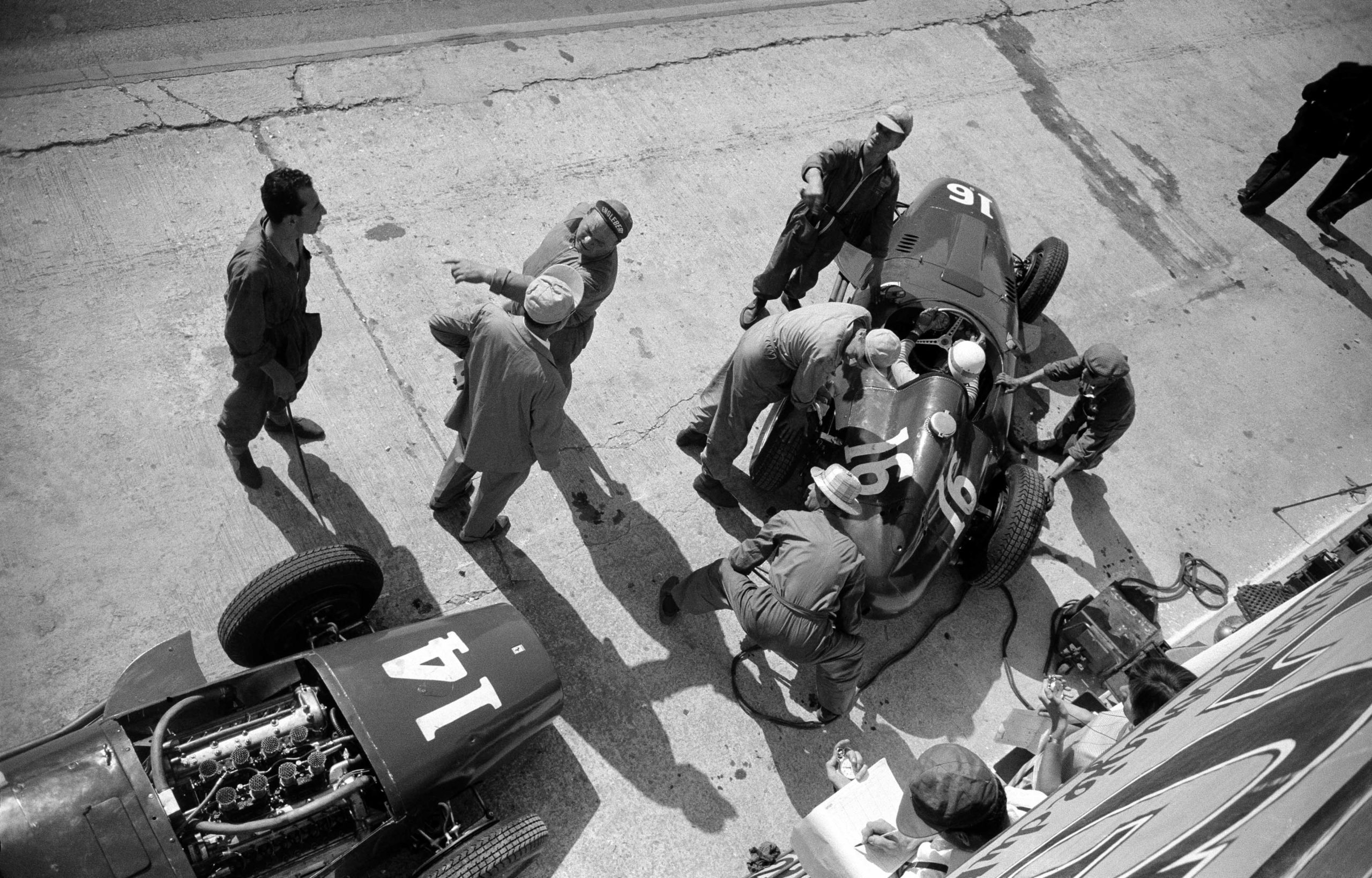 The French Grand Prix; Rouen-les Essarts, July 7, 1957. Here is another wonderful photograph from the 1957 French Grand Prix taken during practice at the Ferrari pits. N. 16 is the car of Maurice Trintignant which is being just fired up and n. 14 is the car for Mike Hawthorn. Meanwhile, mechanic Luigi Parenti directs the orchestra at center stage! (Photo by Klemantaski Collection/Getty Images)