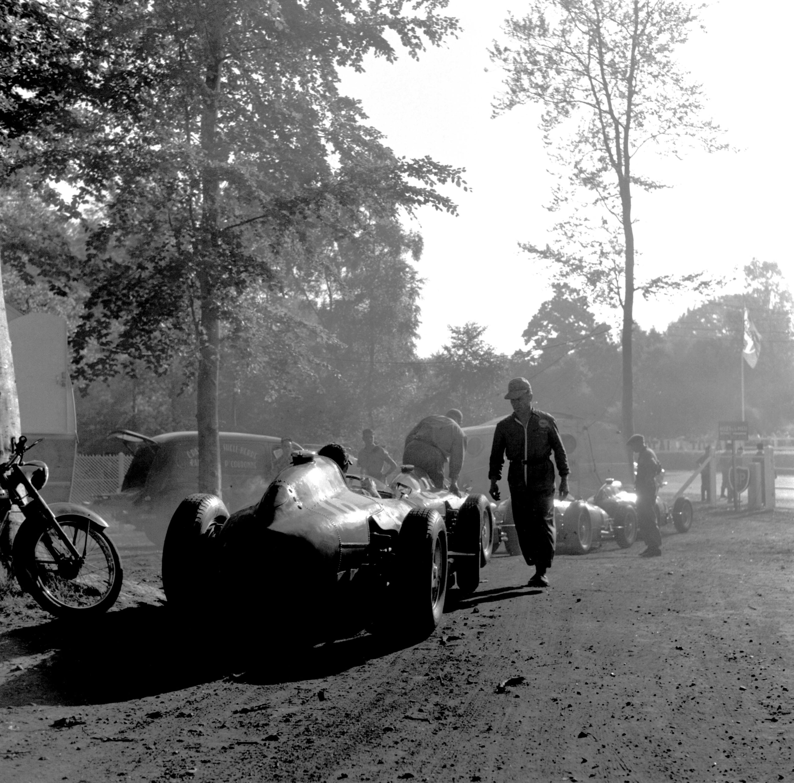 The French Grand Prix; Rouen-les Essarts, July 7, 1957. Early morning in the Rouen paddock which was in a lovely grove of pines � the Ferraris are in line to be fueled before the start. Car n. 16 was to be driven by the FrenchmanMaurice Trintignant, but did not finish. Once again Klemantaski uses the natural composition of the surroundings in early morning to evoke the silence before the thunder of the coming race. In the race itself, Fangiowas totally dominant in his Maserati 250F, presaging his astounding victory at the Nürburgring which would come a month later. Starting from pole position, he finished almost a minute ahead of Musso�s Ferrari. (Photo by Klemantaski Collection/Getty Images)