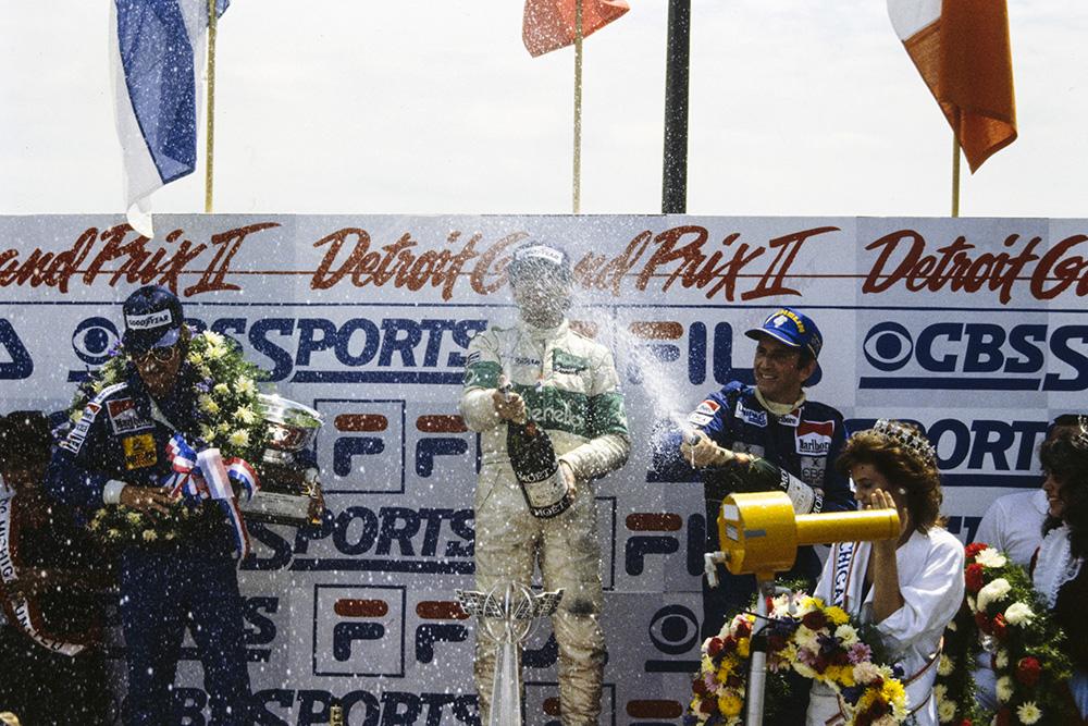Michele Alboreto, 1st position, celebrates on the podium with Keke Rosberg, 2nd position, and John Watson, 3rd position on the podium.