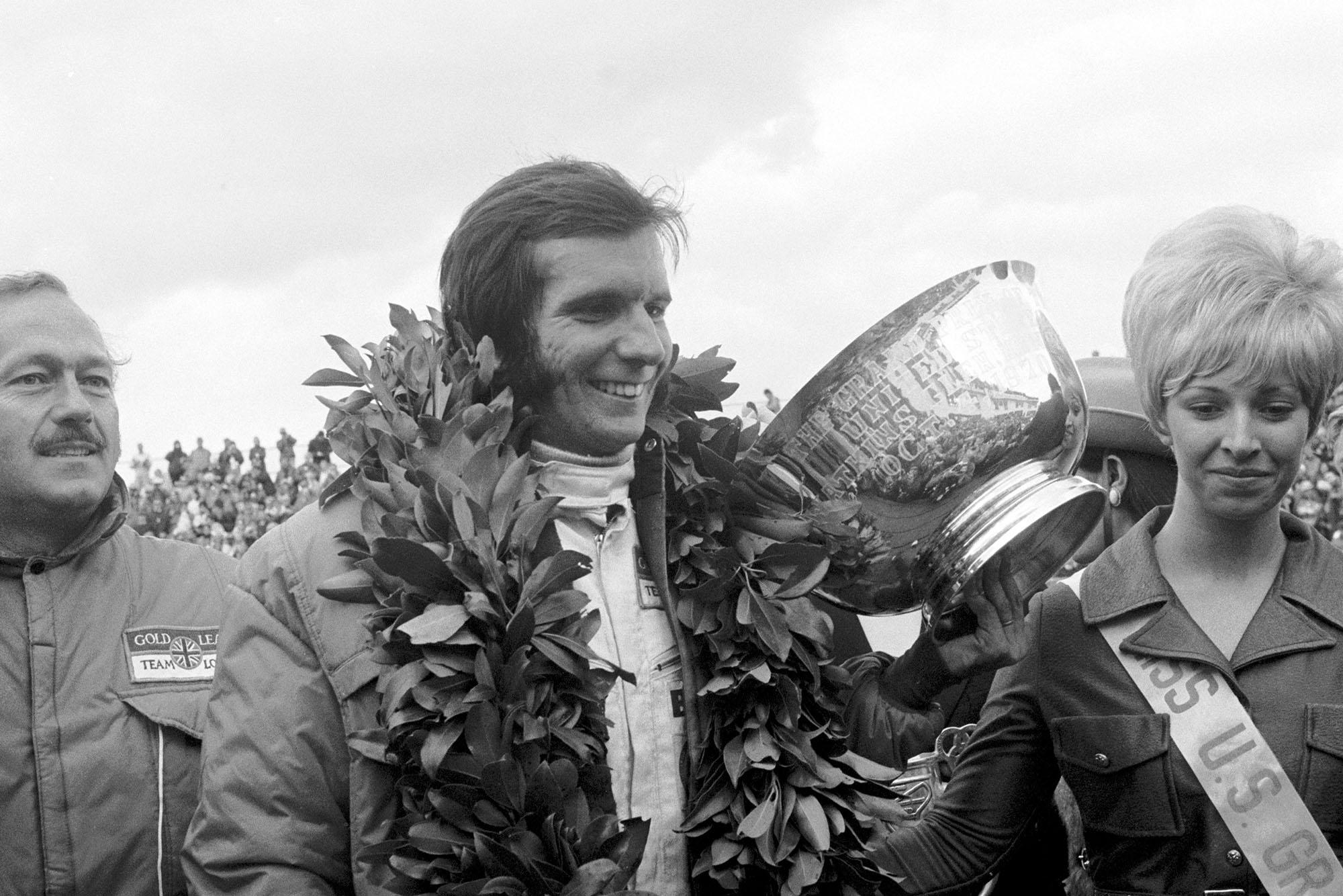 Emerson Fittipaldi celebrates on the podium after winning the 1970 United States Grand Prix