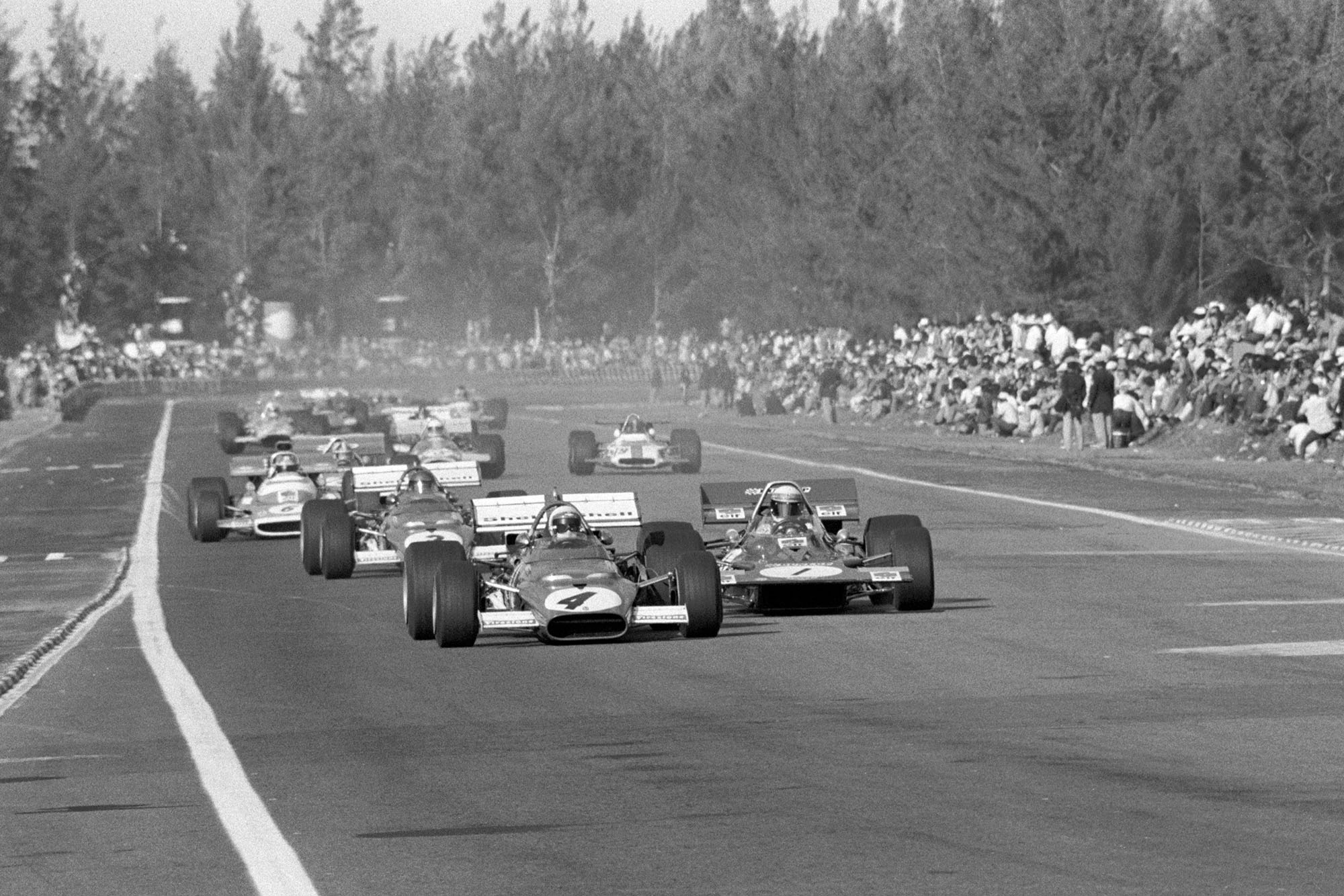 Clay Regazzoni's Ferrari leads the field on the opening lap of the Mexican Grand Prix.