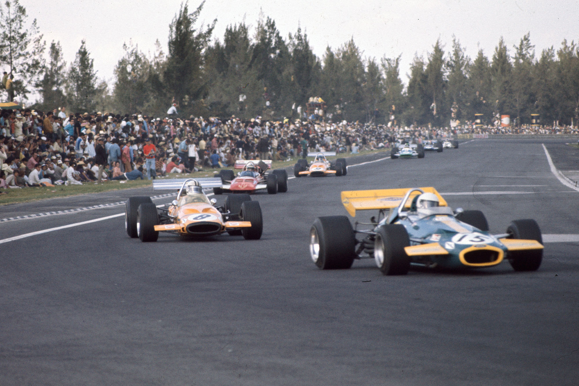 Large crowds gather dangerously near to the track as the race continues at the 1970 Mexican Grand Prix.
