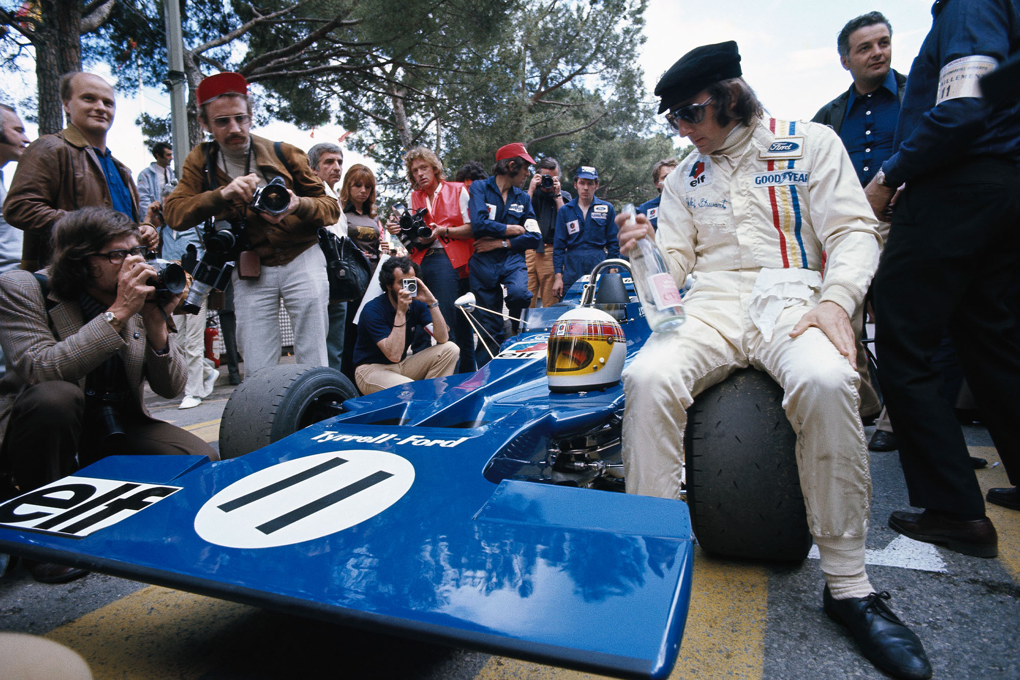 Jackie Stewart sits on the wheel of his Tyrrell before the 1971 Monaco Grand Prix.