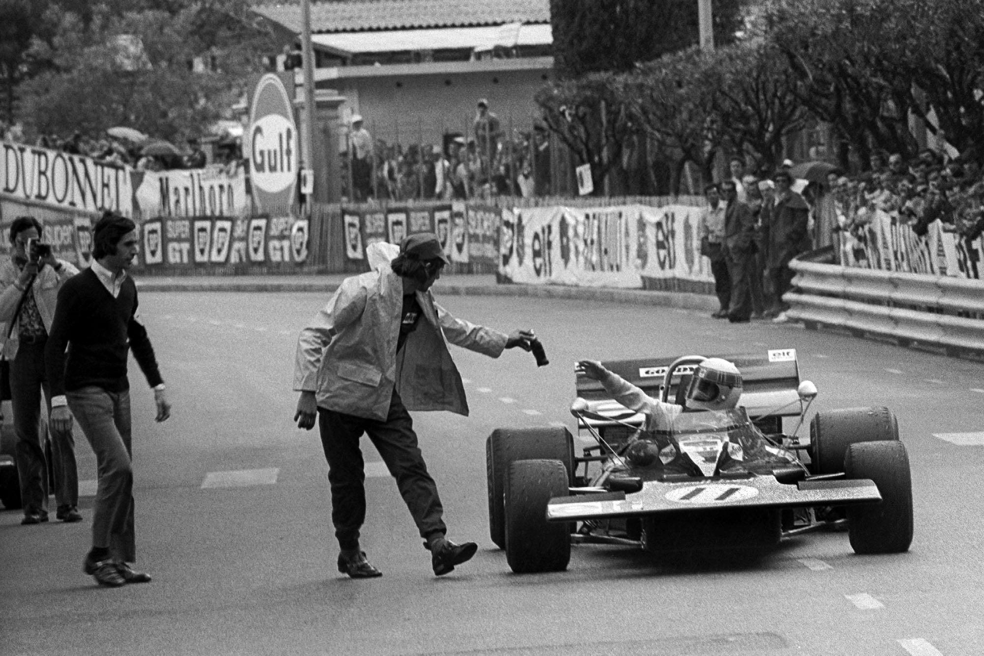 Jackie Stewart is handed a drink as he pulls up after winning the 1971 Monaco Grand Prix.
