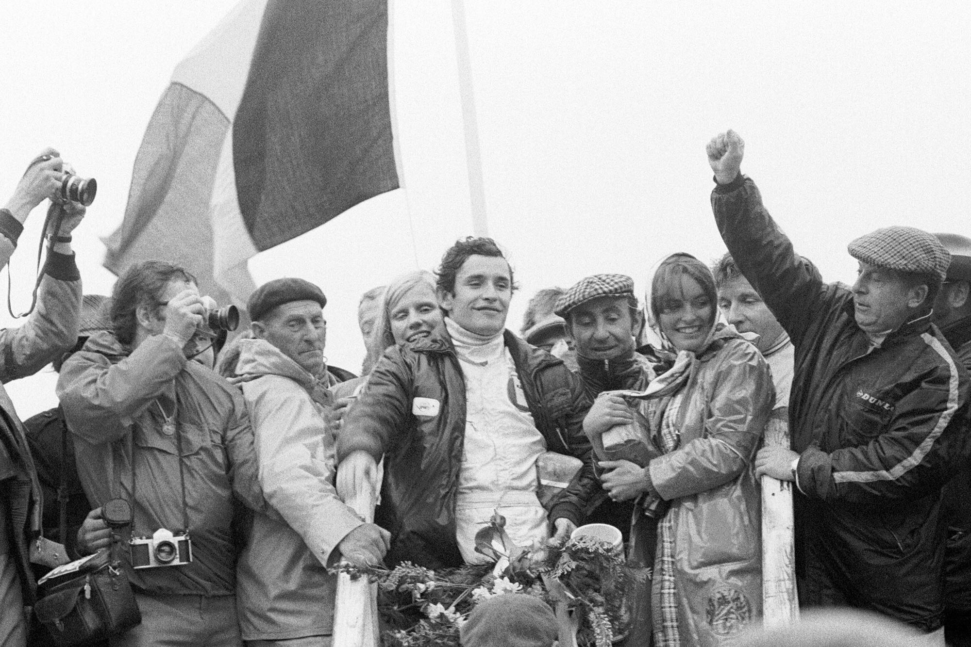 Jacky Ickx celebrates his win on the podium after emerging victorious at the 1971 Dutch Grand Prix.