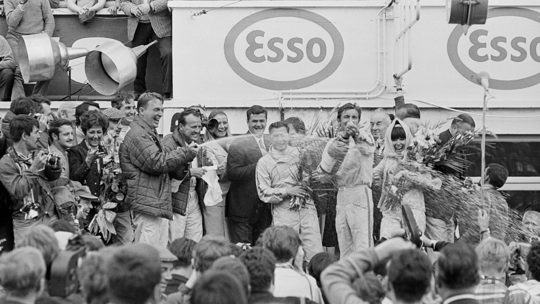 Dan Gurney and AJ Foyt spray champagne on the podium after the 1967 Le Mans 24 Hours