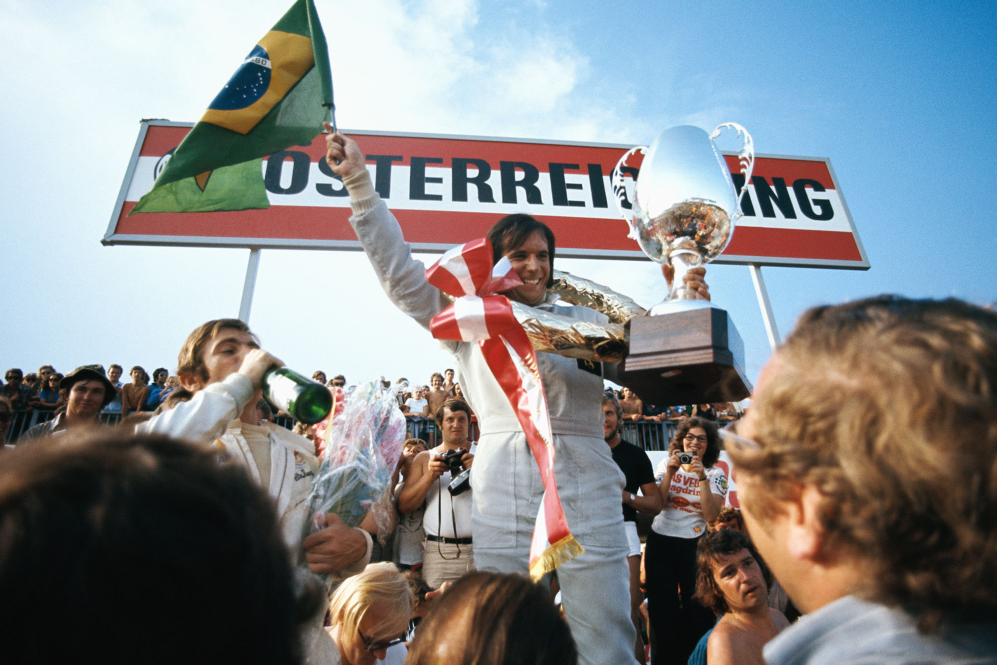 Emerson Fittipaldi holds his trophy and the Brazilian flag aloft after winning the 1972 Austrian Grand Prix.