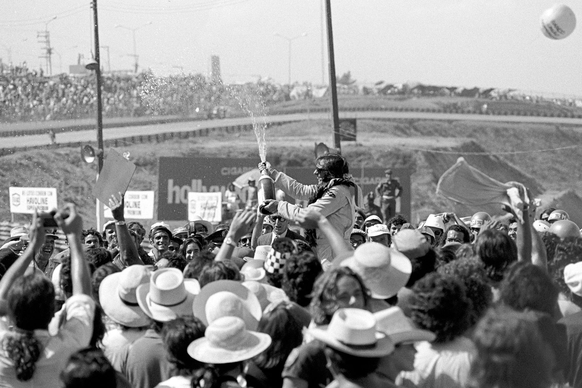 Emerson Fittipaldi (Lotus) sprays the champagne on the podium after winning the 1973 Brazilian Grand Prix.