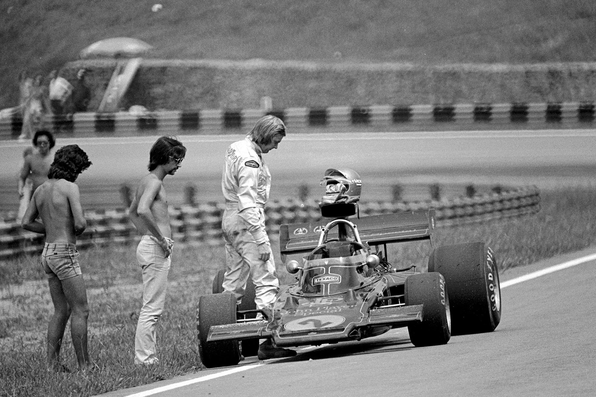 Ronnie Peterson inspects his Lotus car after retiring from the 1973 Brazilian Grand Prix.