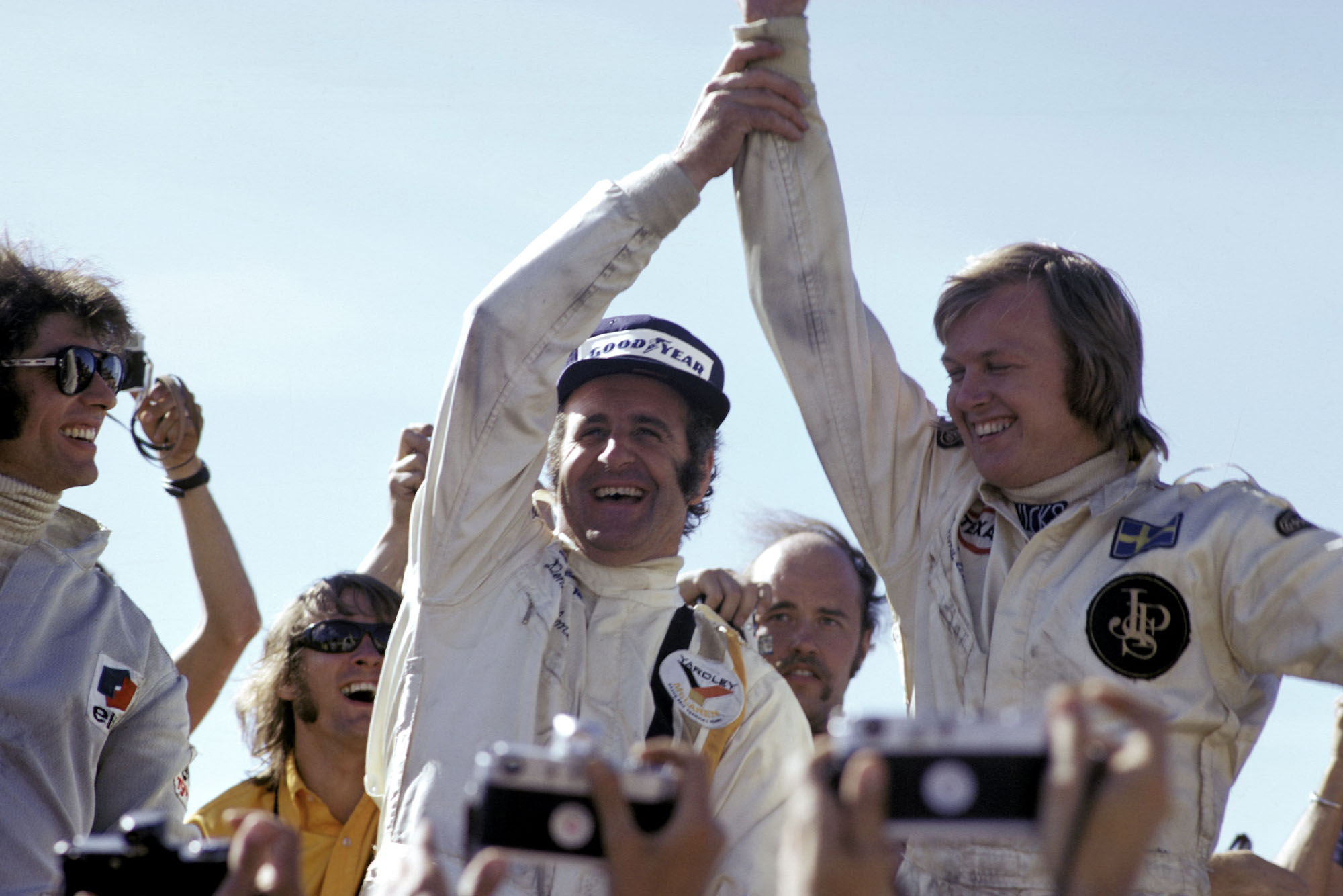 Denny Hulme (McLaren) and Ronnie Peterson (Lotus) celebrate on the podium.