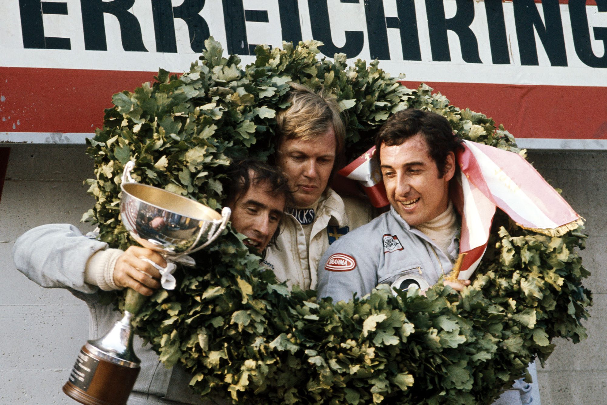 Ronnie Peterson (centre), Jackie Stewart (left) and Carlos Pace (right) celebrate on the podium at the 1973 Austrian Grand Prix.